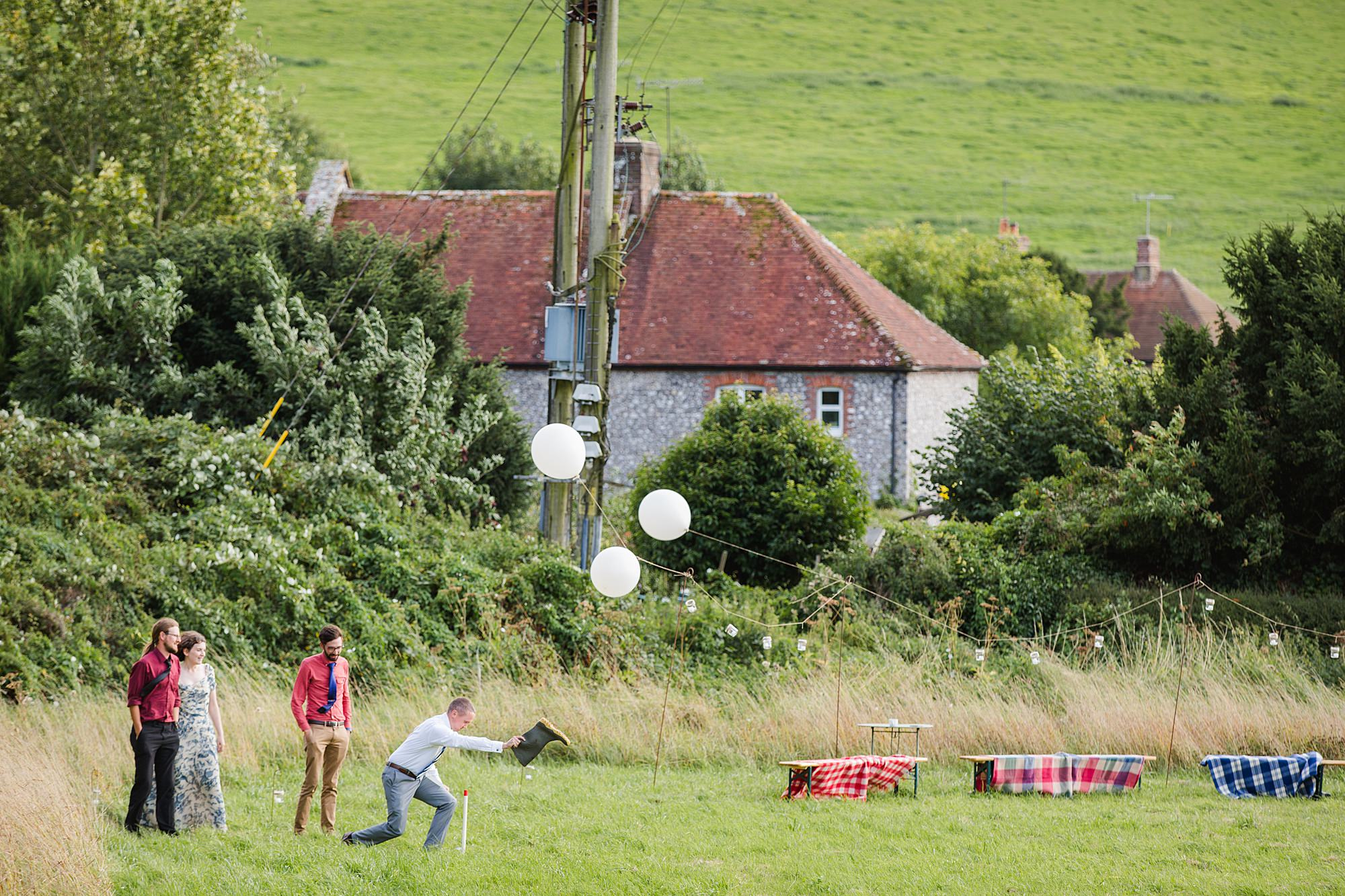 Fun village hall wedding guests playing toss the horse shoe