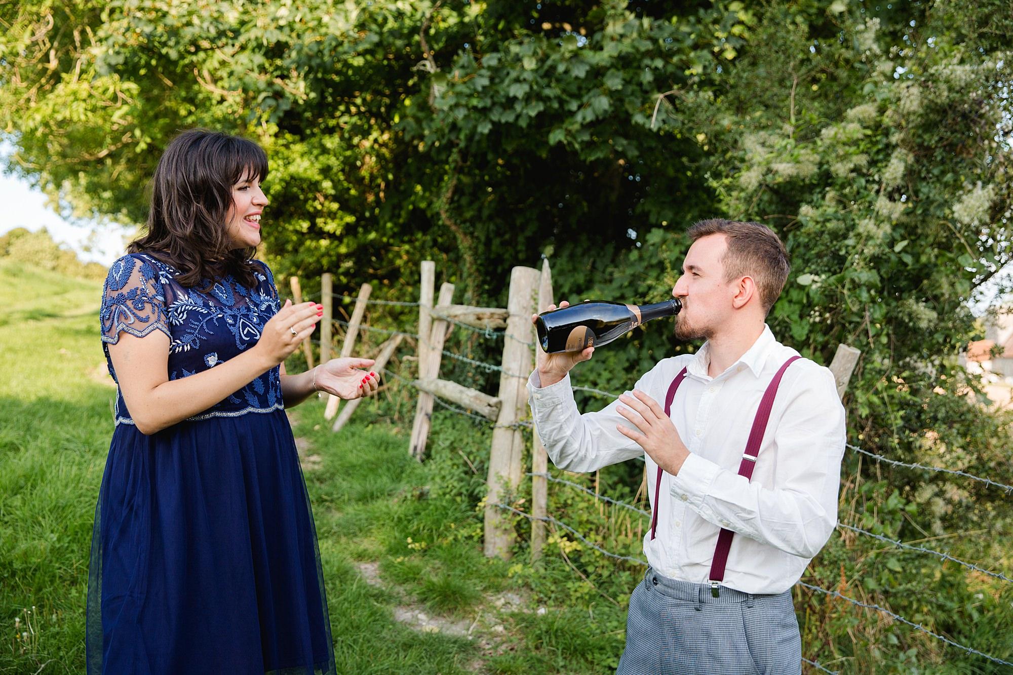 Fun village hall wedding groomsman drinking champagne from the bottle