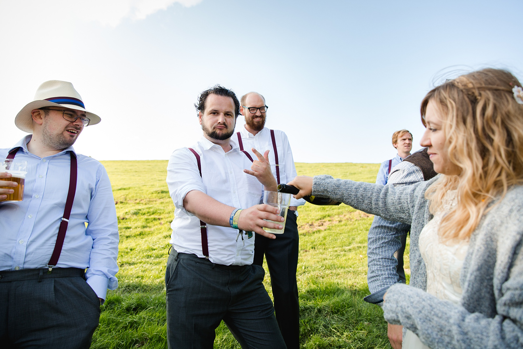 Fun village hall wedding bride pours champagne for groomsman
