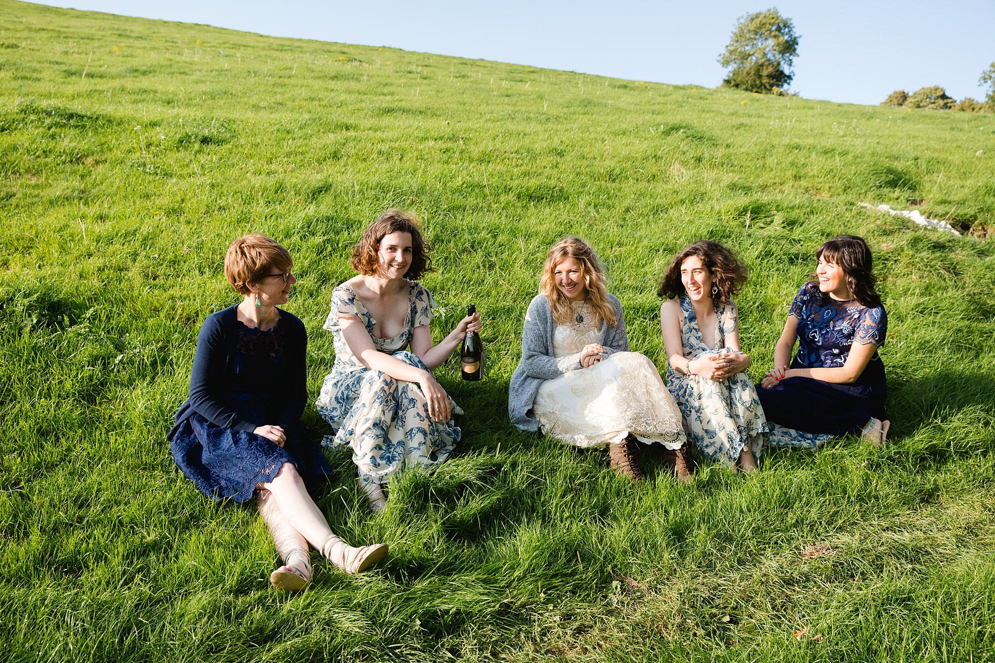 Fun village hall wedding bride and bridesmaids sit on grass together