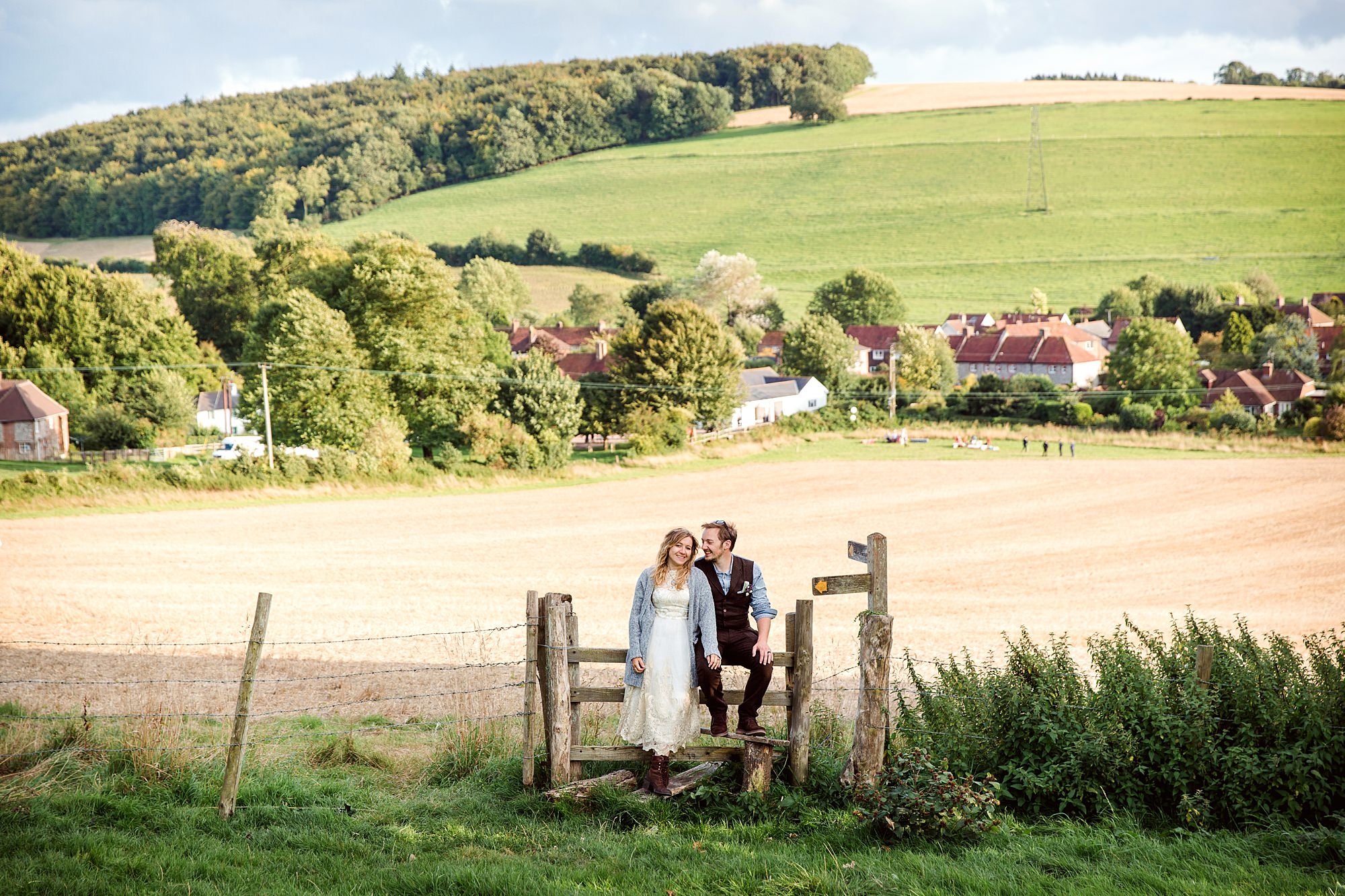 Fun village hall wedding bride and groom together in field