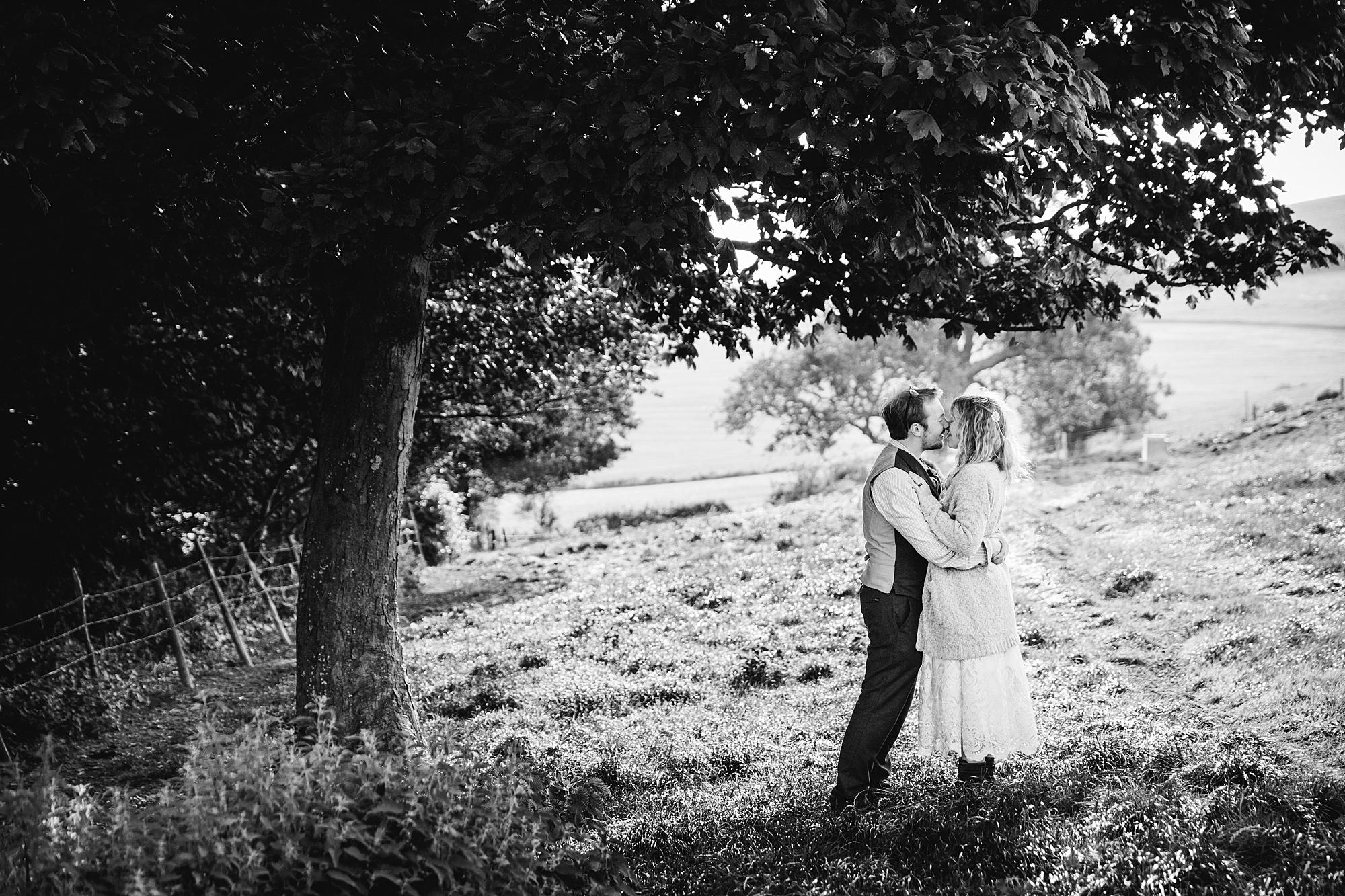 Fun village hall wedding bride and groom kiss under a tray