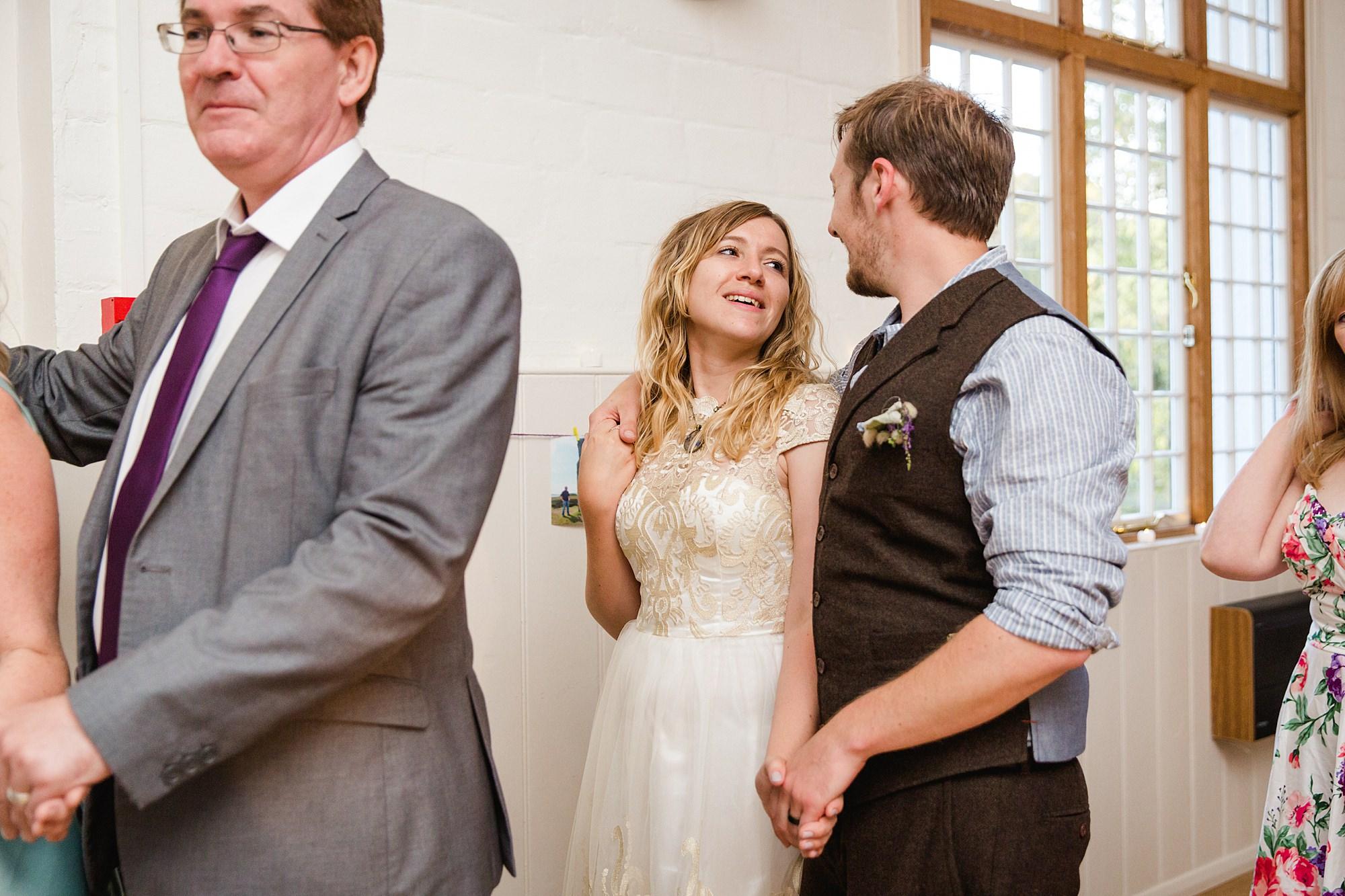 Fun village hall wedding bride and groom enjoying ceilidh dance