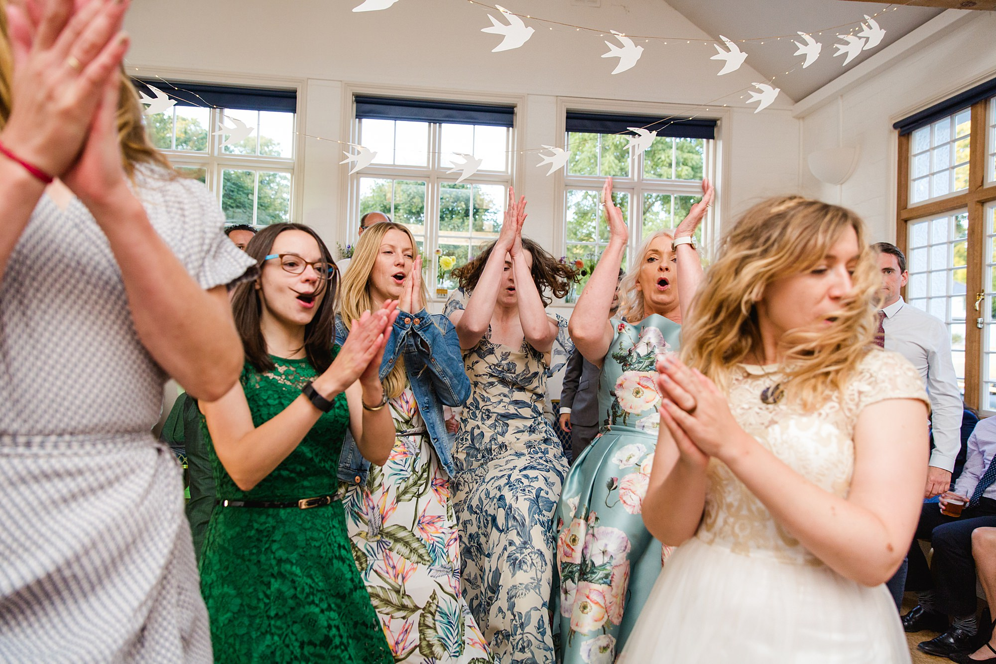 Fun village hall wedding guests clapping together in ceilidh dance