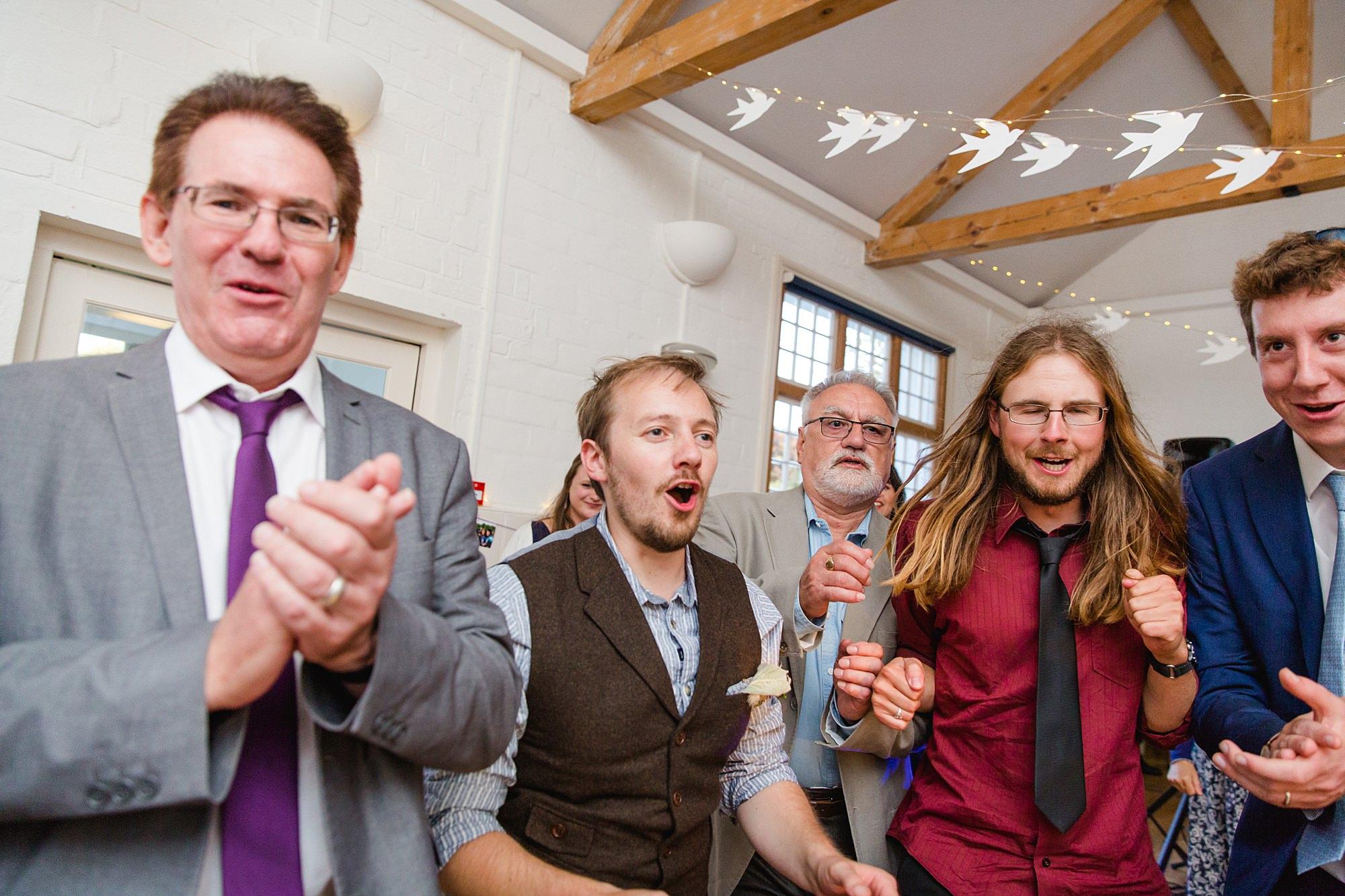 Fun village hall wedding groom and friends dancing in ceilidh