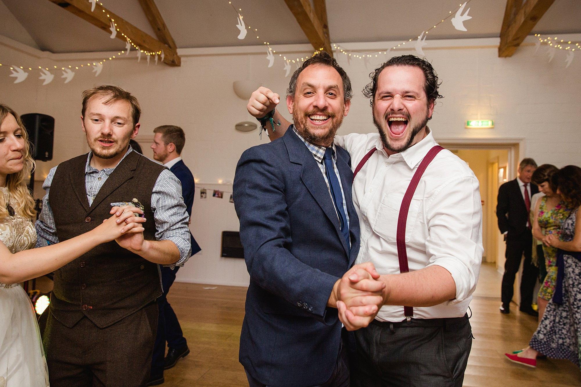 Fun village hall wedding groomsmen laughing during ceilidh