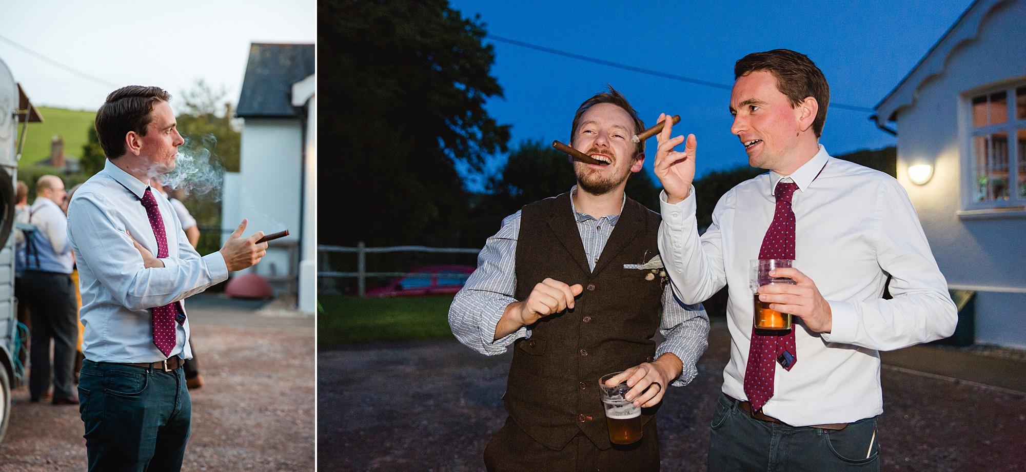 Fun village hall wedding groom and friends smoke cigars together