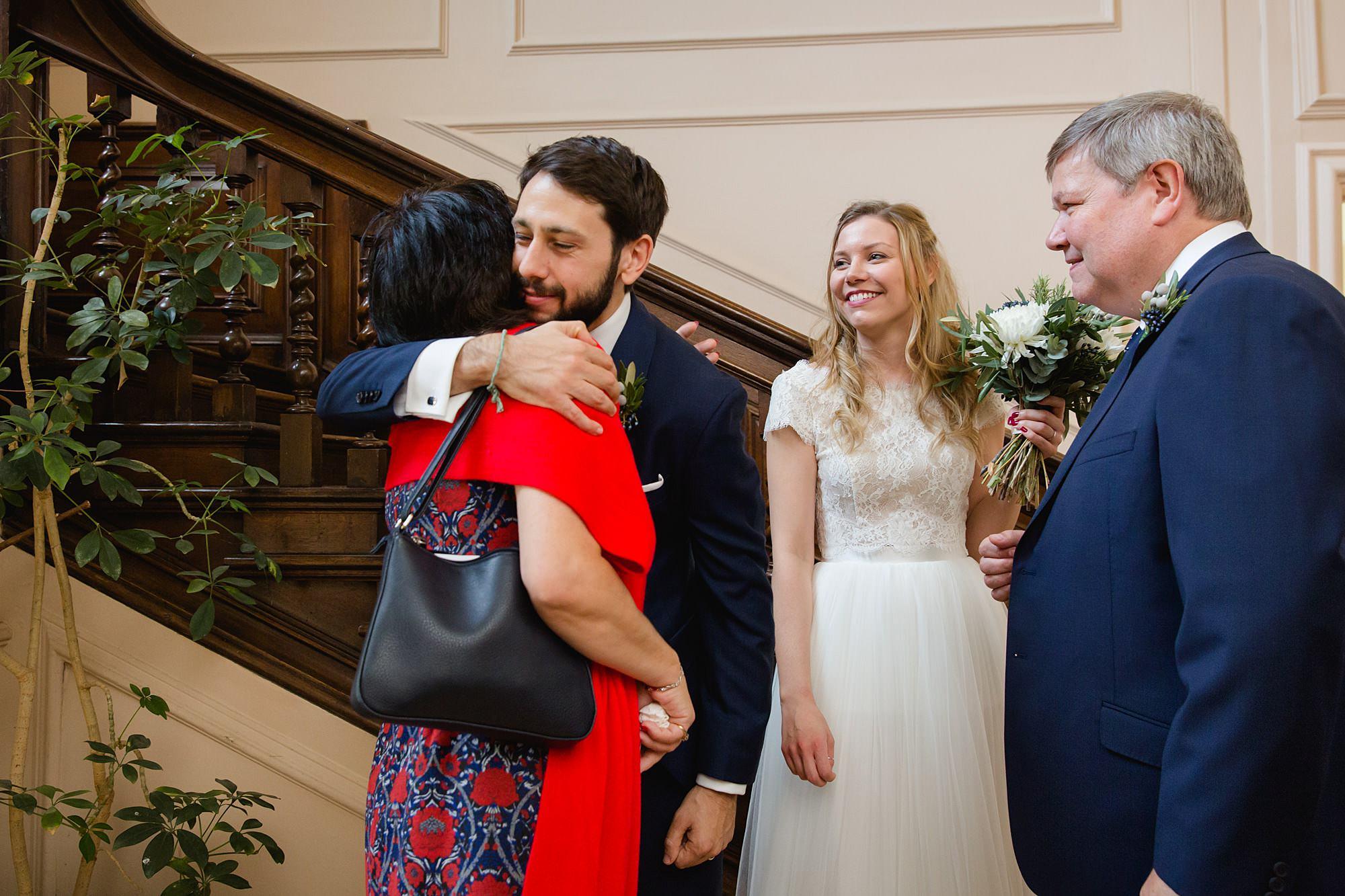 shaw house wedding groom hugs guest