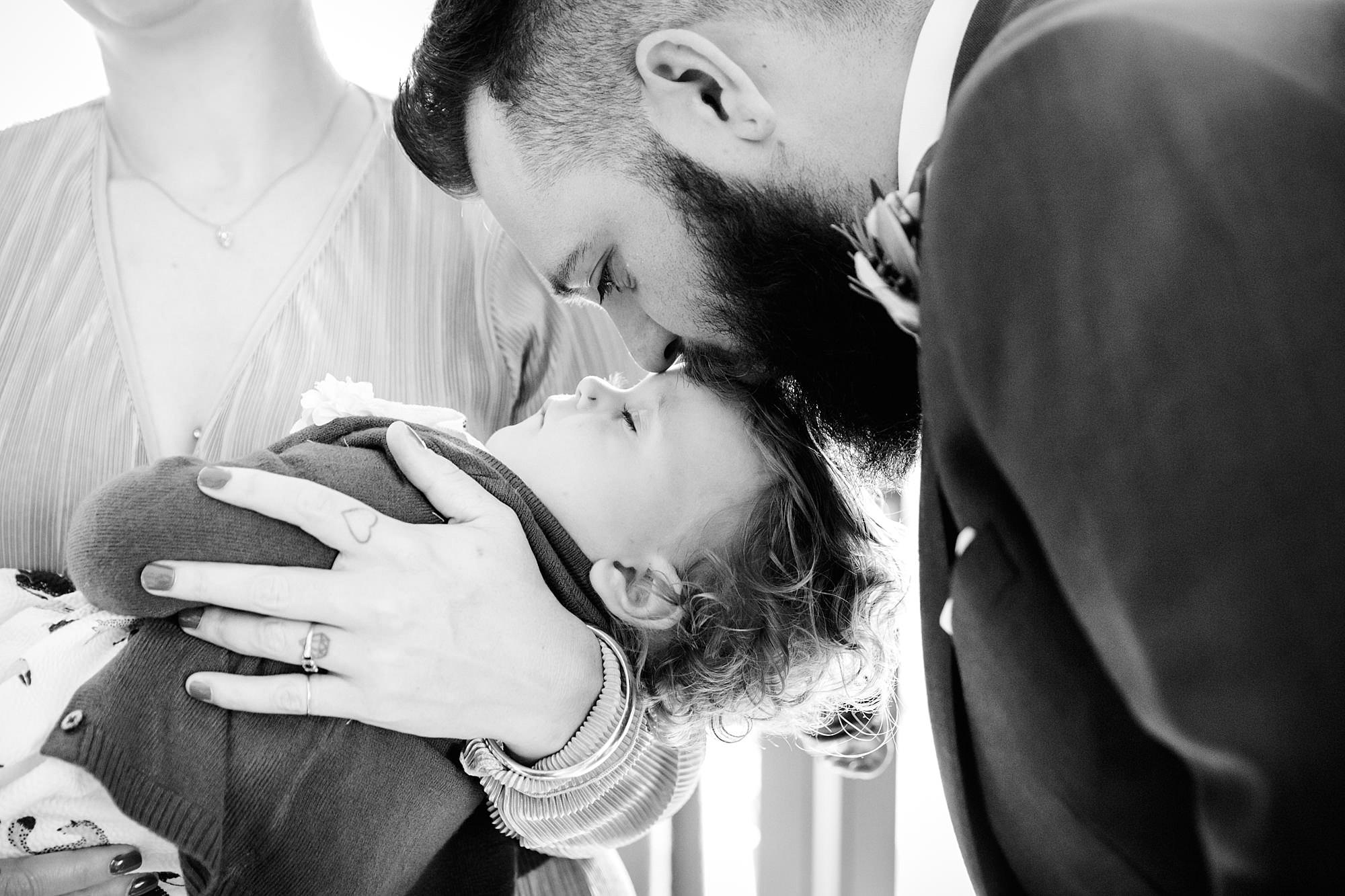 shaw house wedding guest kisses their child on forehead