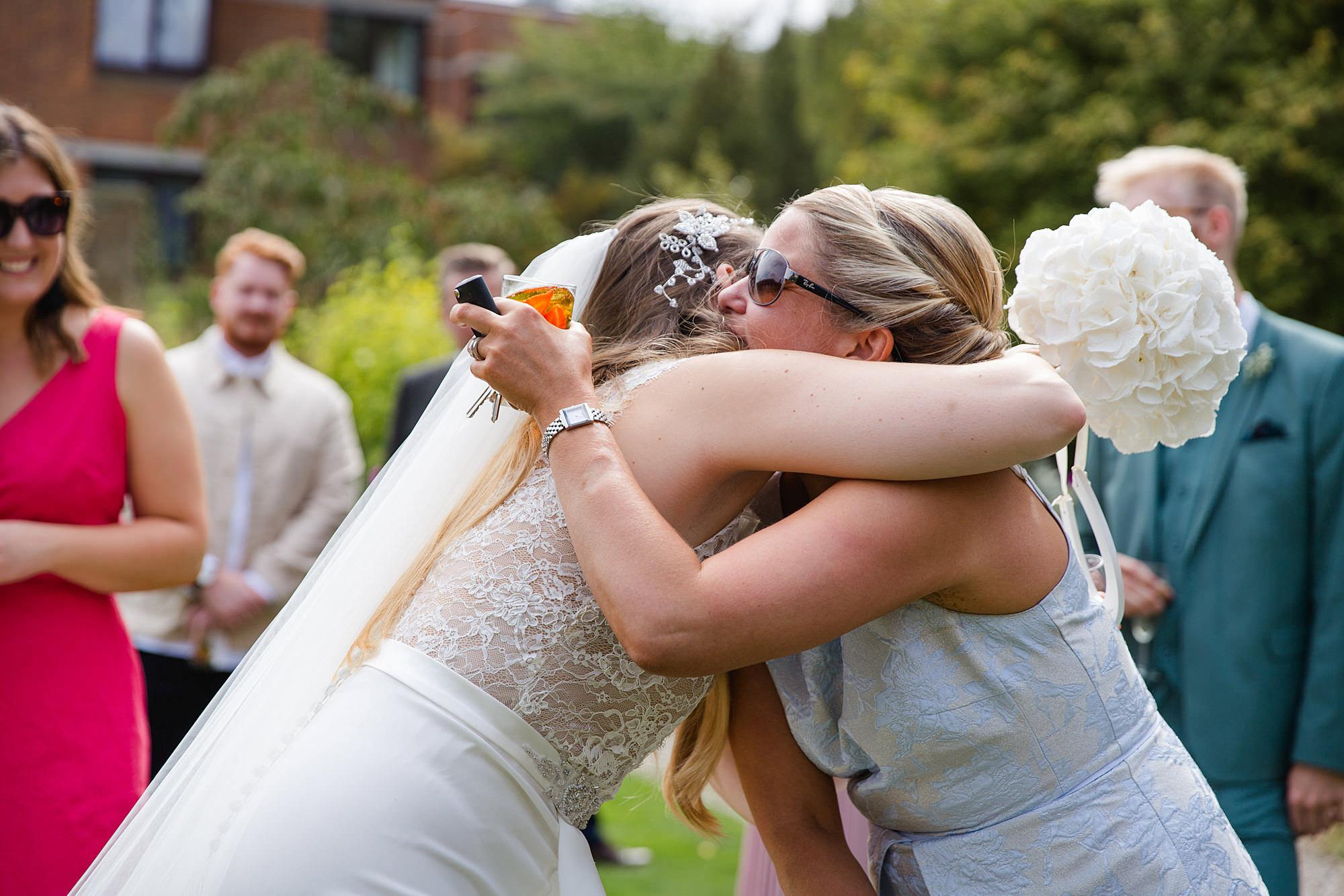 Writtle university college wedding guest hugs bride