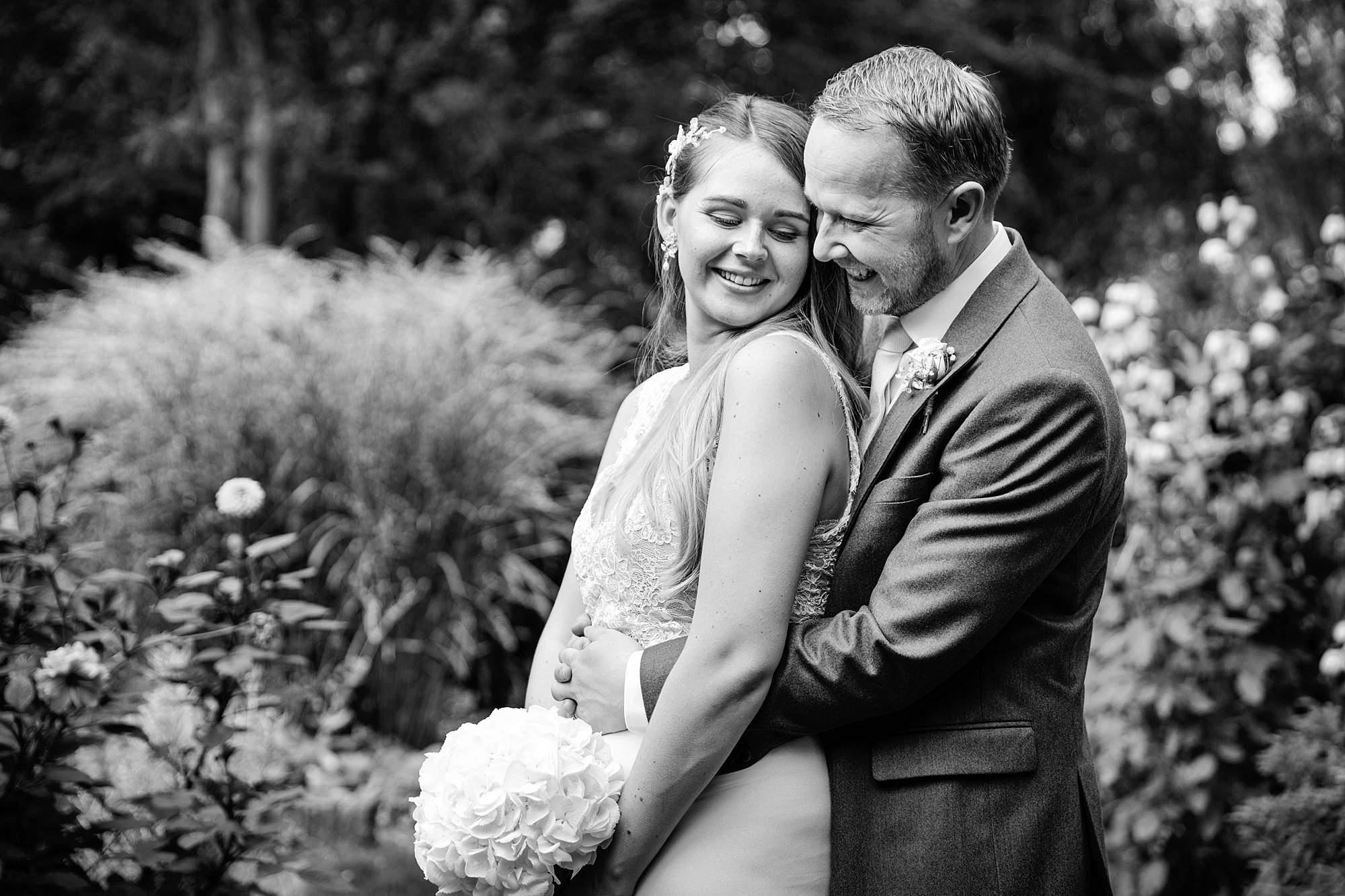 Writtle university college wedding groom hugs bride in gardens