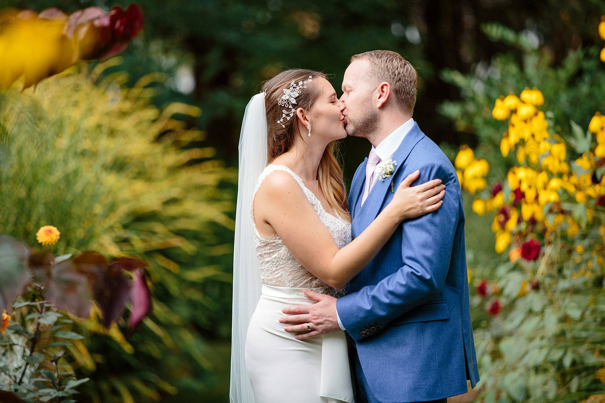 Writtle university college wedding bride and groom kiss amongst flowers