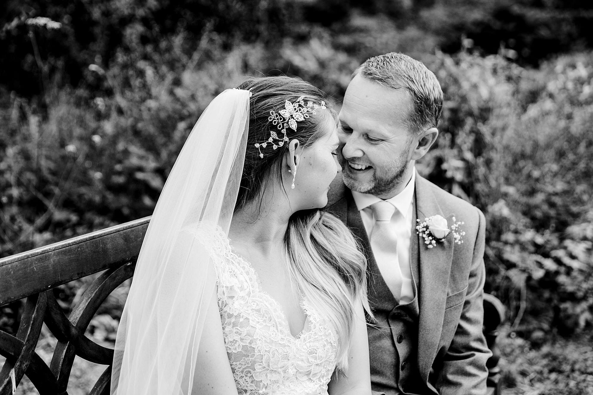 Writtle university college wedding bride and groom talk on bench