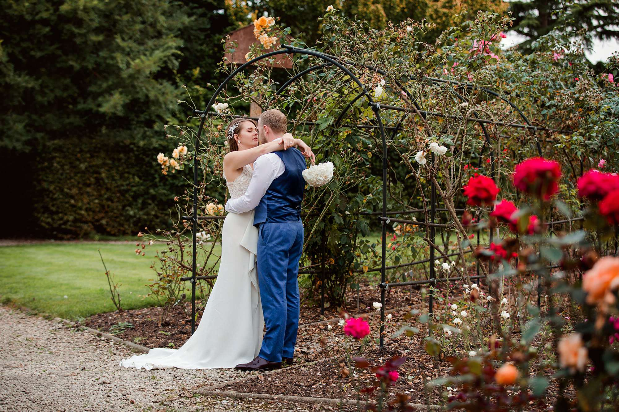 Writtle university college wedding bride and groom kiss in rose garden