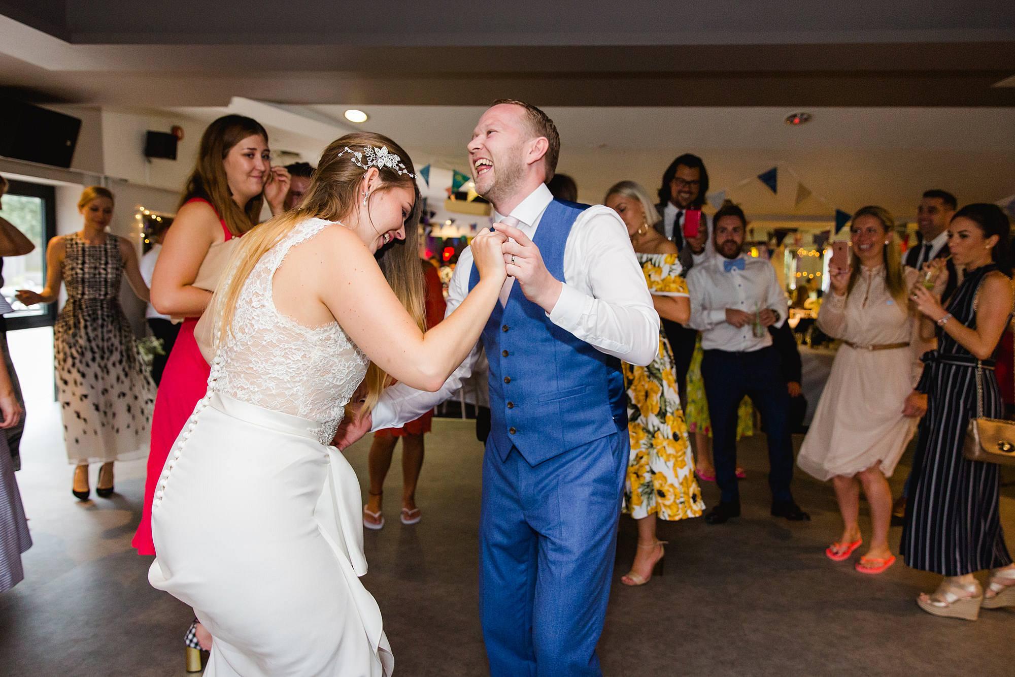 fun portrait of bride and groom dancing