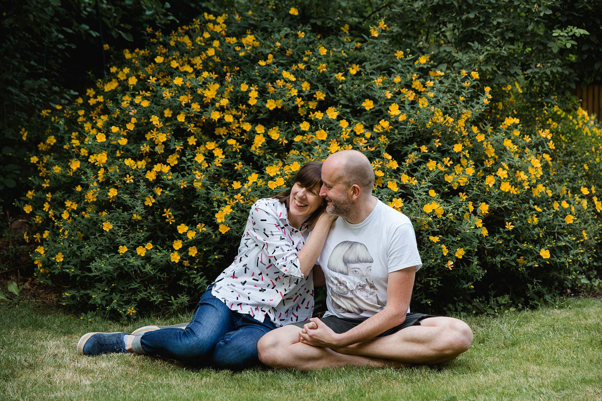 engagement shoot with cat couple sit together on grass