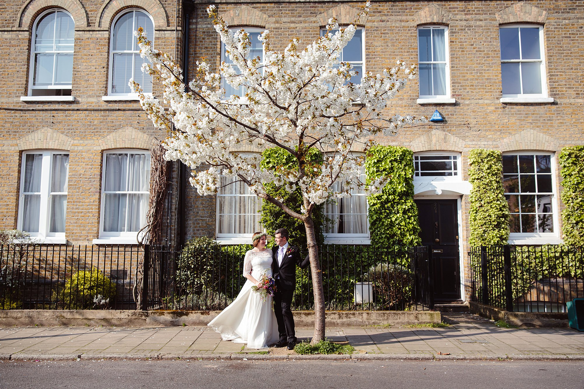 fun london wedding bowling bride and groom by blossom tree