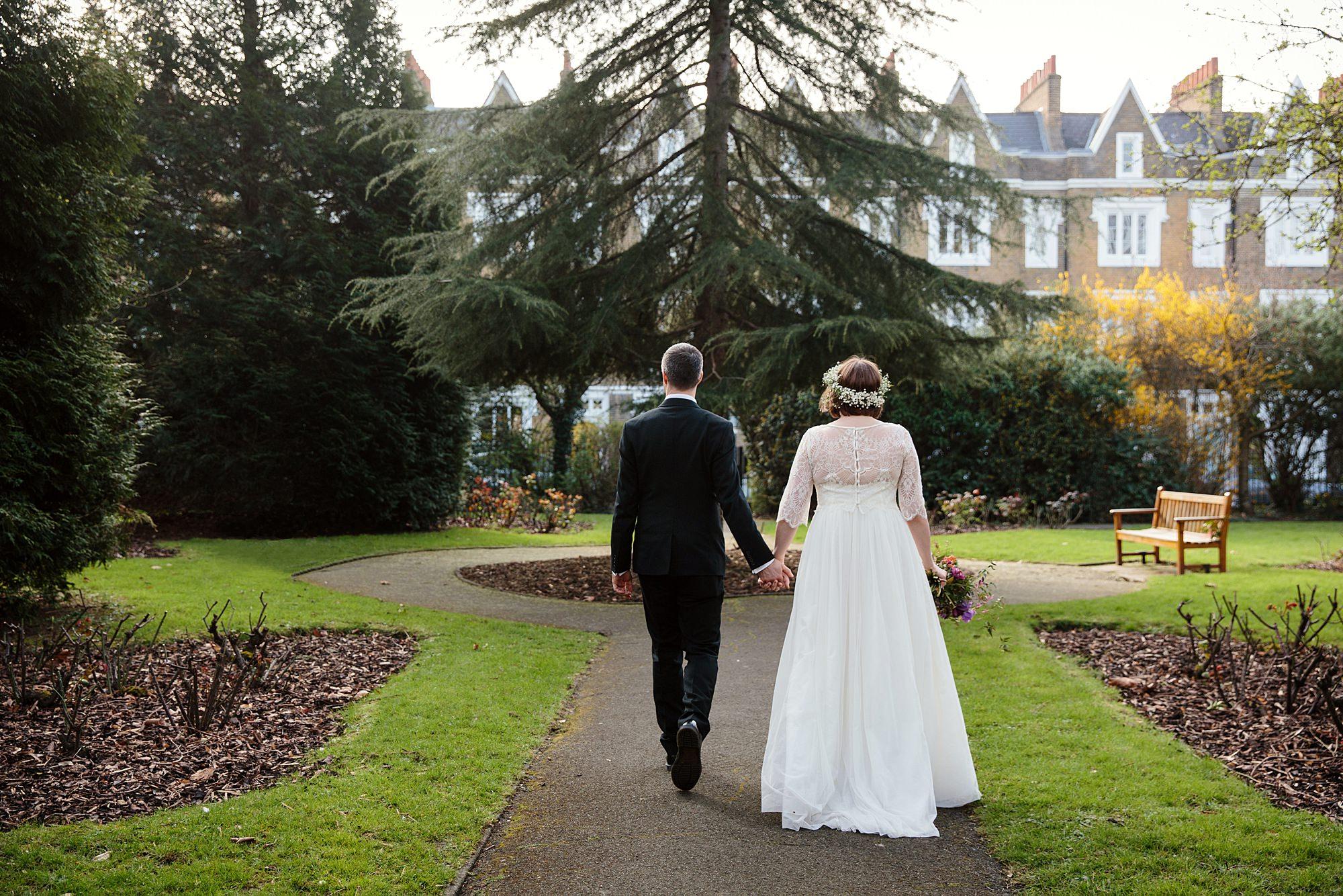 fun london wedding bowling bride and groom walking through gardens