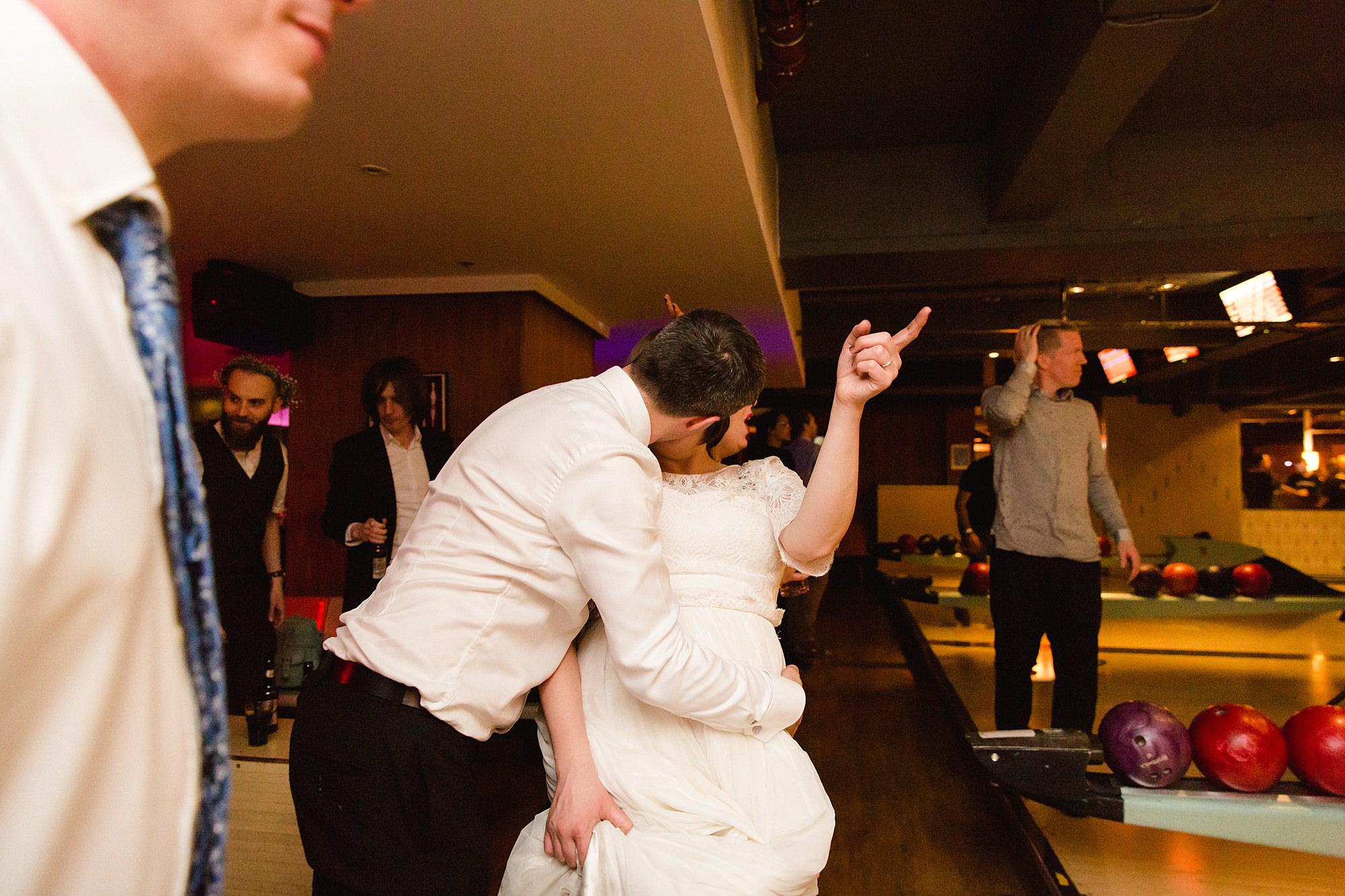fun london wedding bowling groom kisses bride
