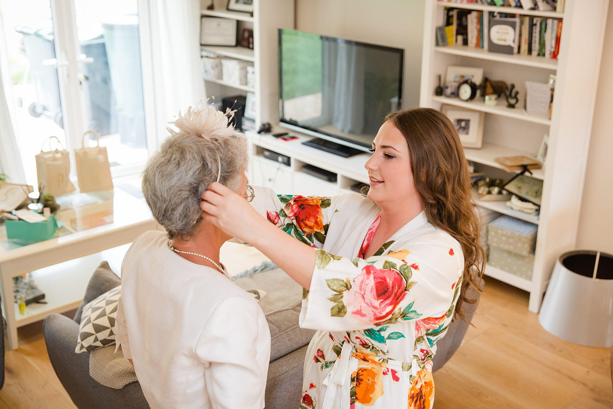 fun outdoor wedding bride help's her mum with fascinator
