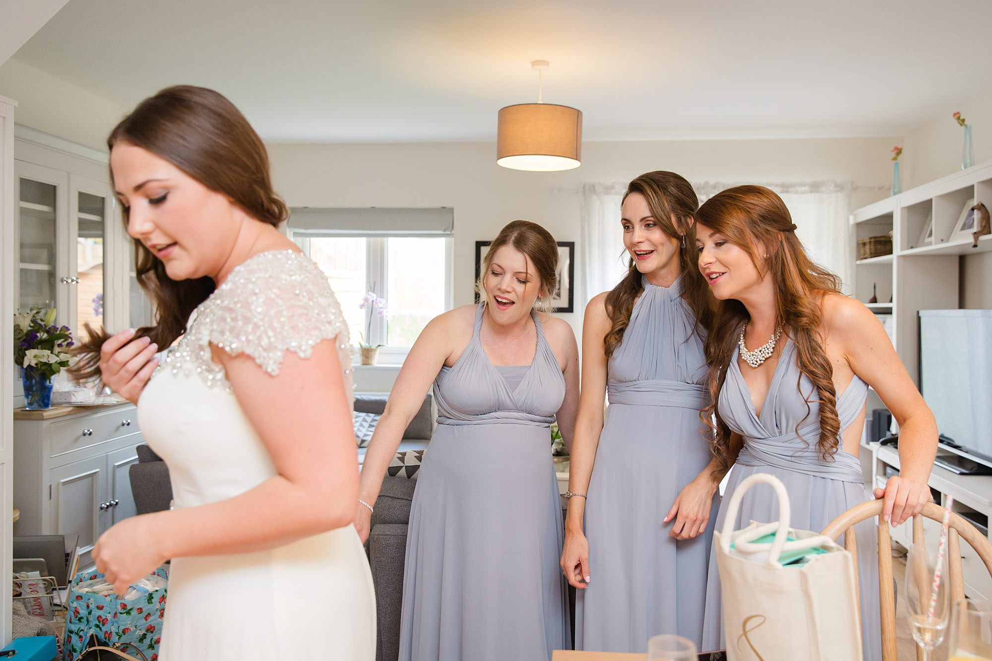 fun outdoor wedding bridesmaids help bride with dress