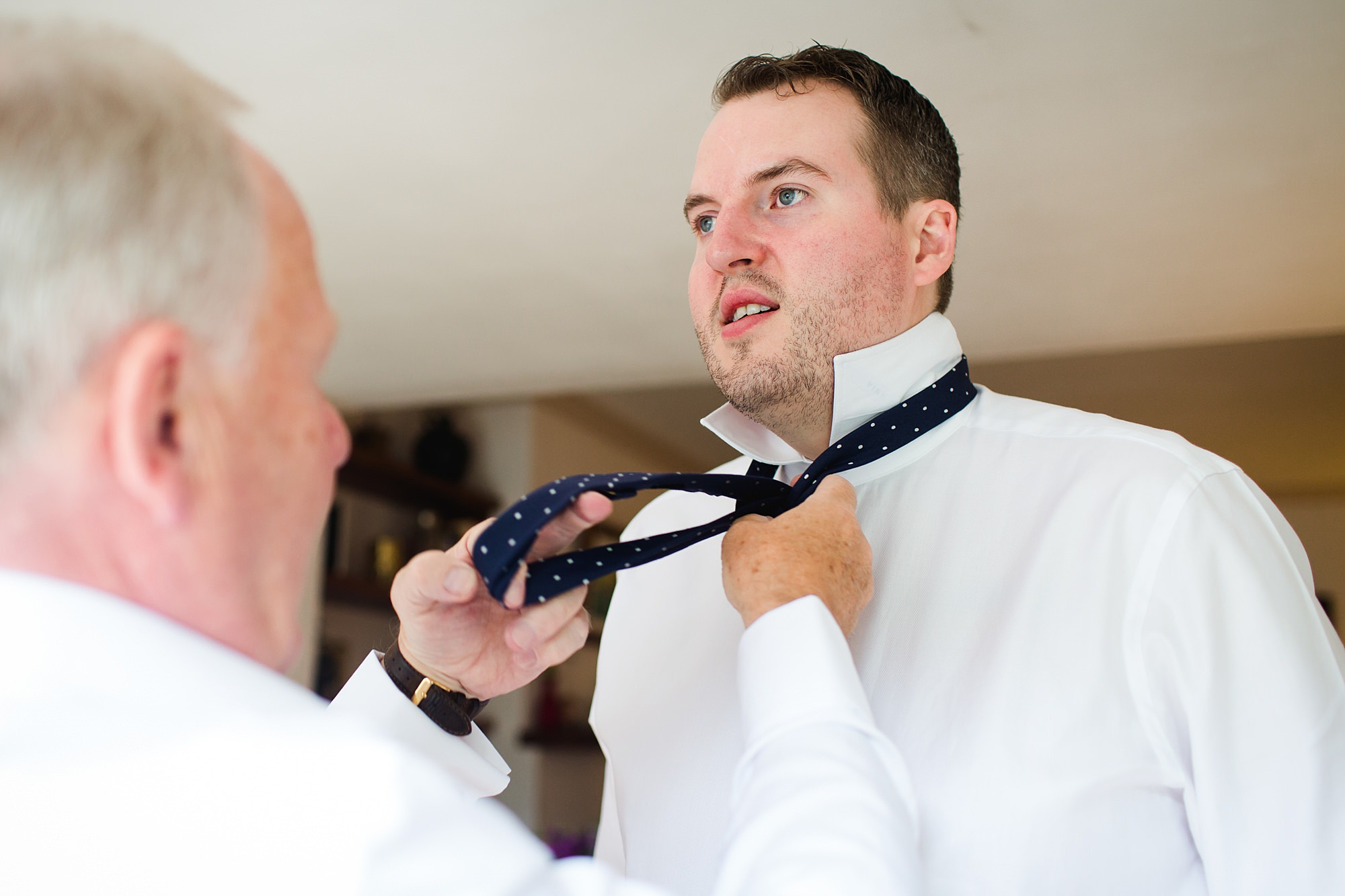fun outdoor wedding groom's dad helps him with his tie