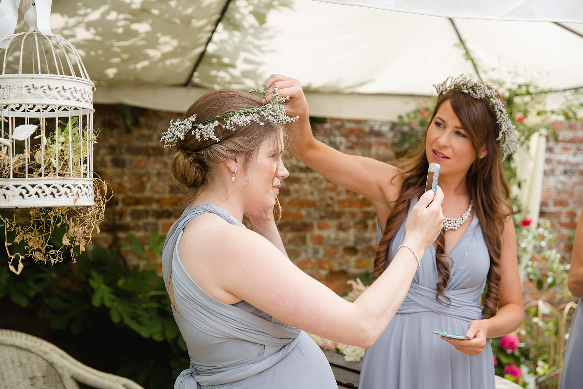 fun outdoor wedding bridesmaid puts on flower crown