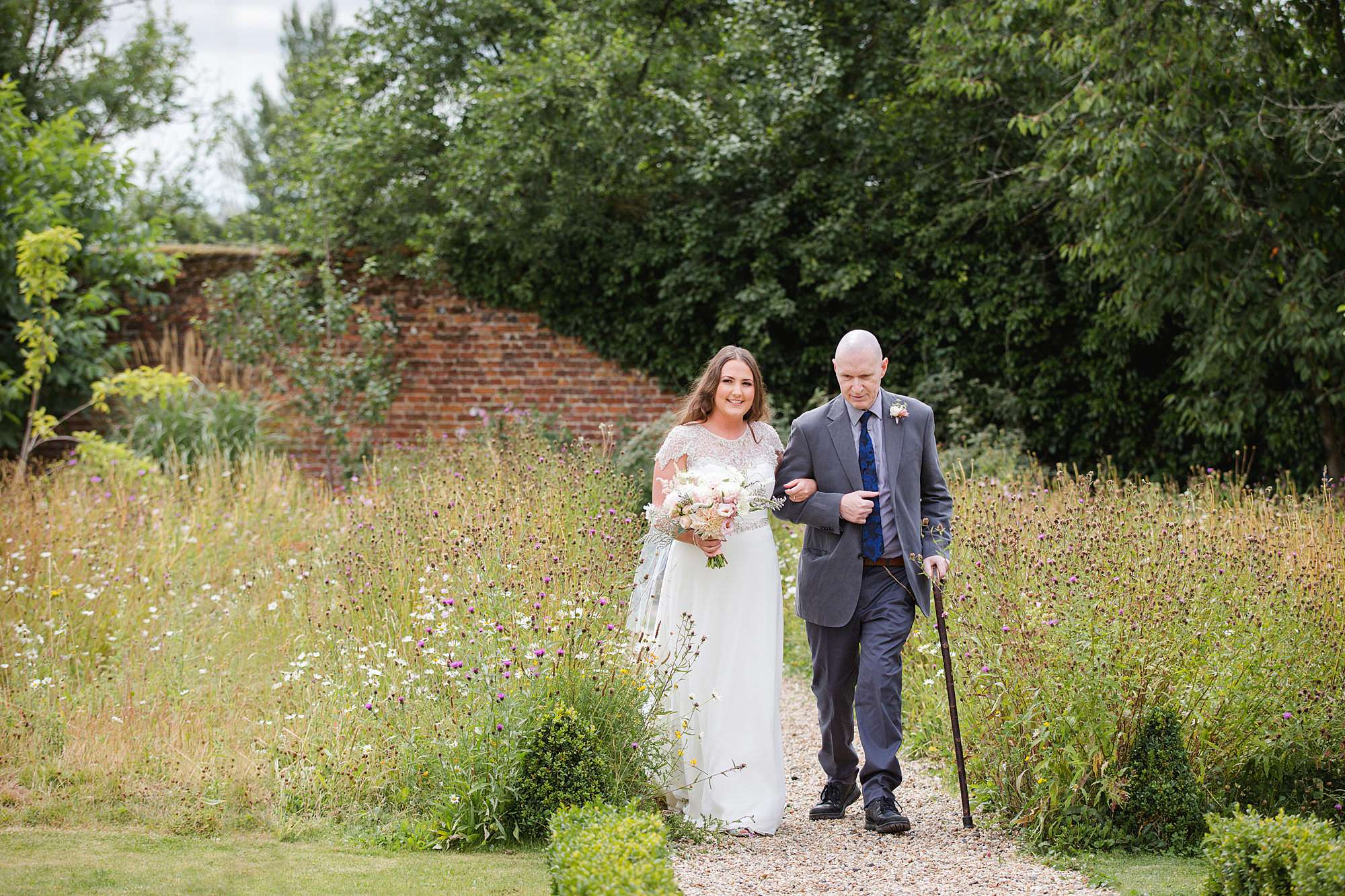 fun outdoor wedding bride walks down garden aisle