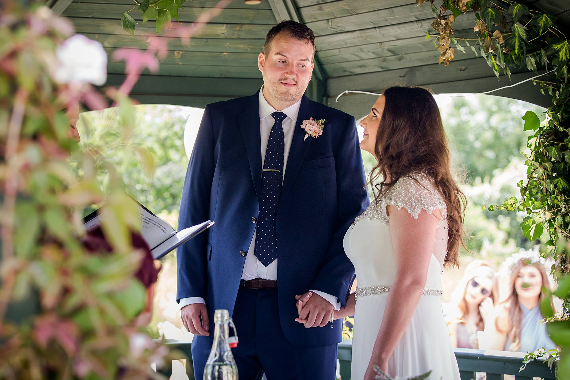 fun outdoor wedding bride and groom exchange vows at secret garden