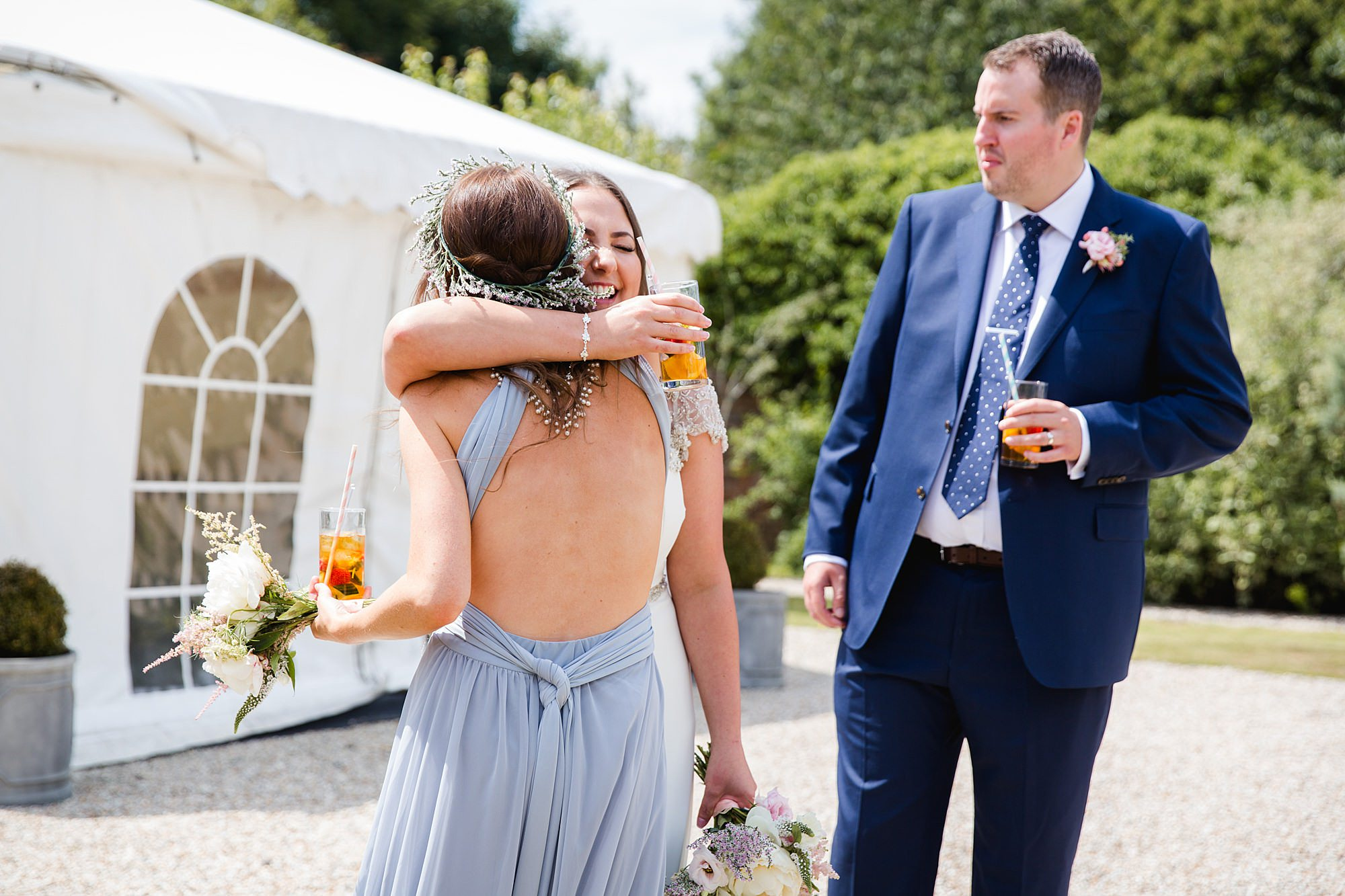 fun outdoor wedding bride hugs bridesmaid