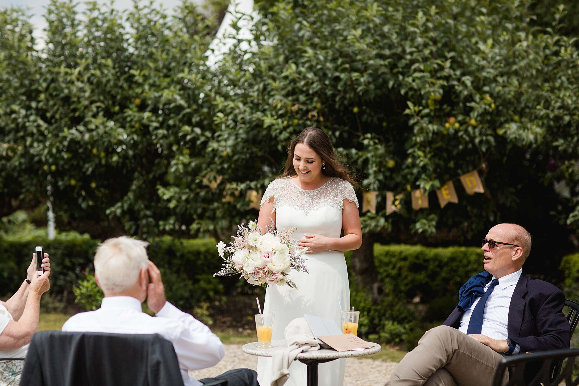 fun outdoor wedding bride shows off her bouquet to guests
