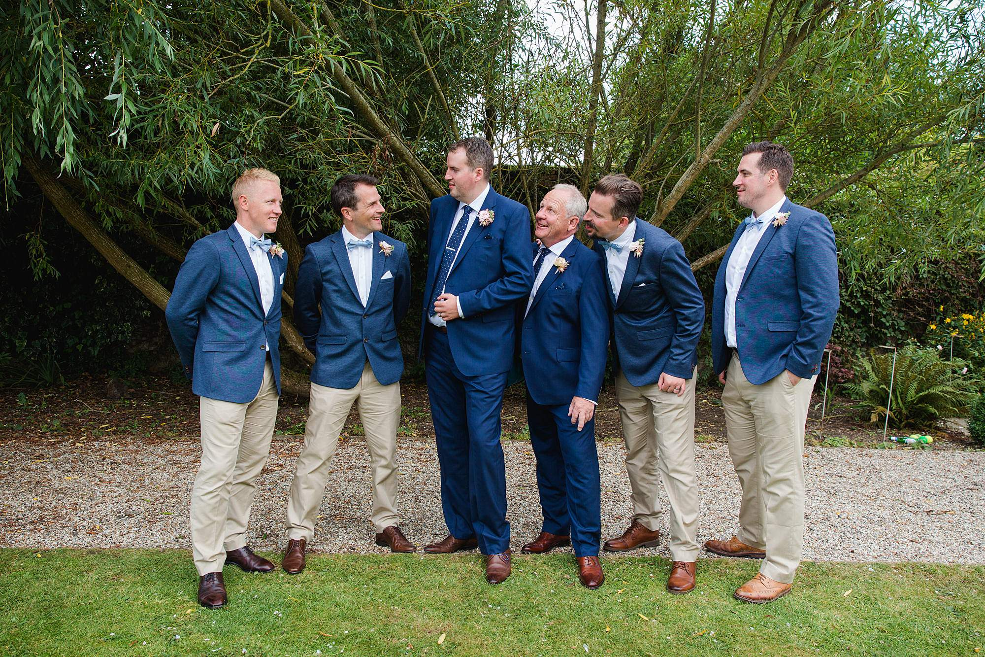 fun outdoor wedding groom laughing his his groomsmen