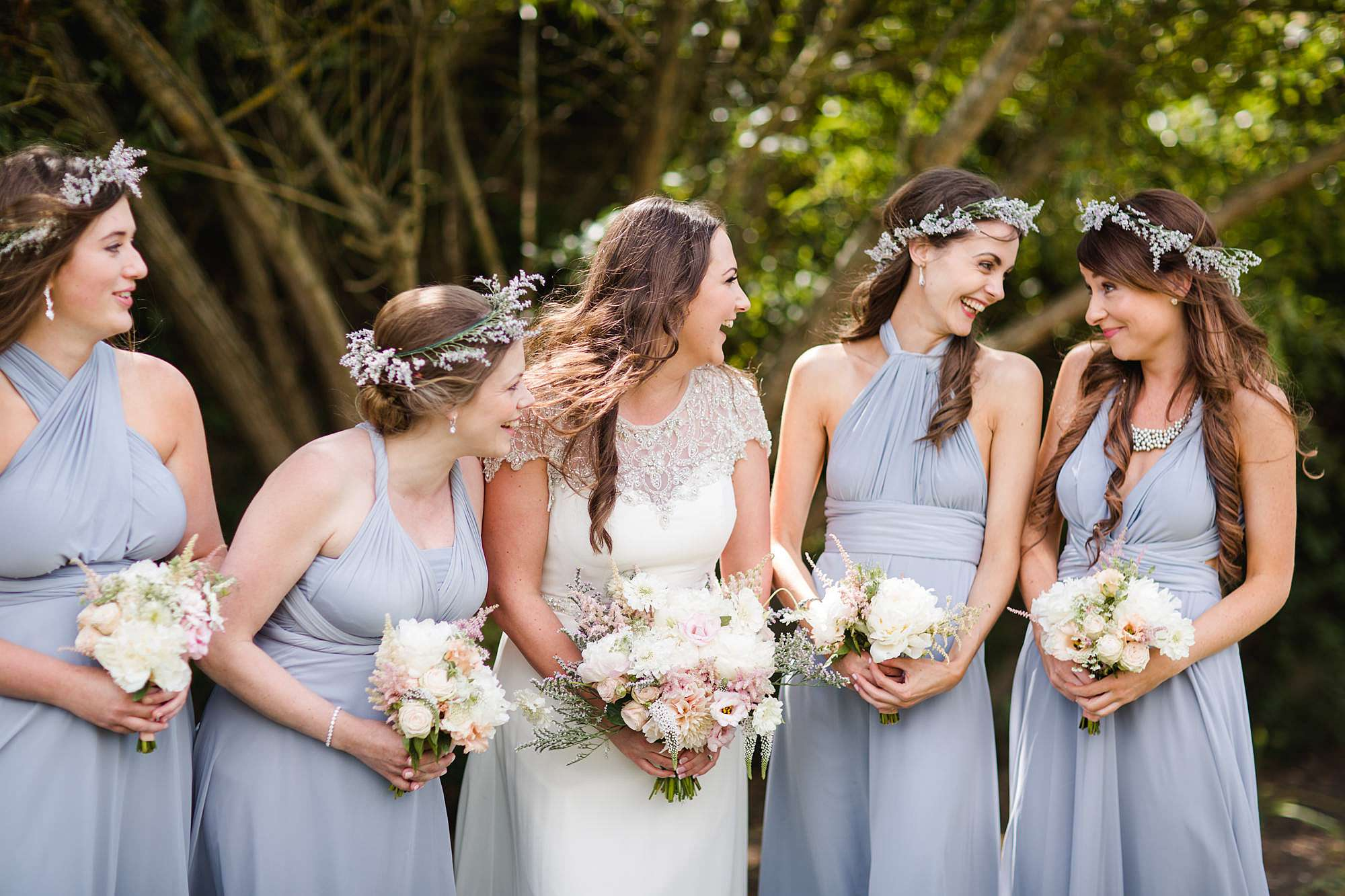 fun outdoor wedding bride and bridesmaids laugh together