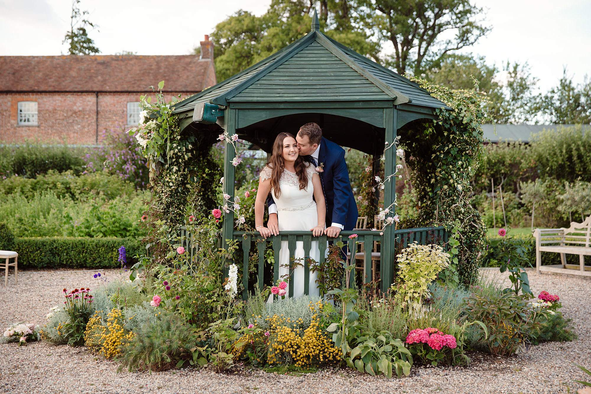 fun outdoor wedding bride and groom in floral gazebo at secret garden