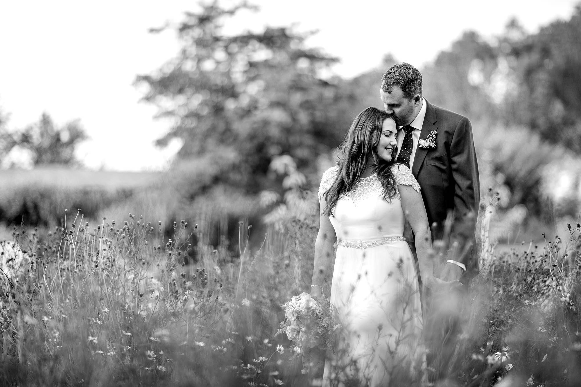 fun outdoor wedding groom kisses bride in the gardens