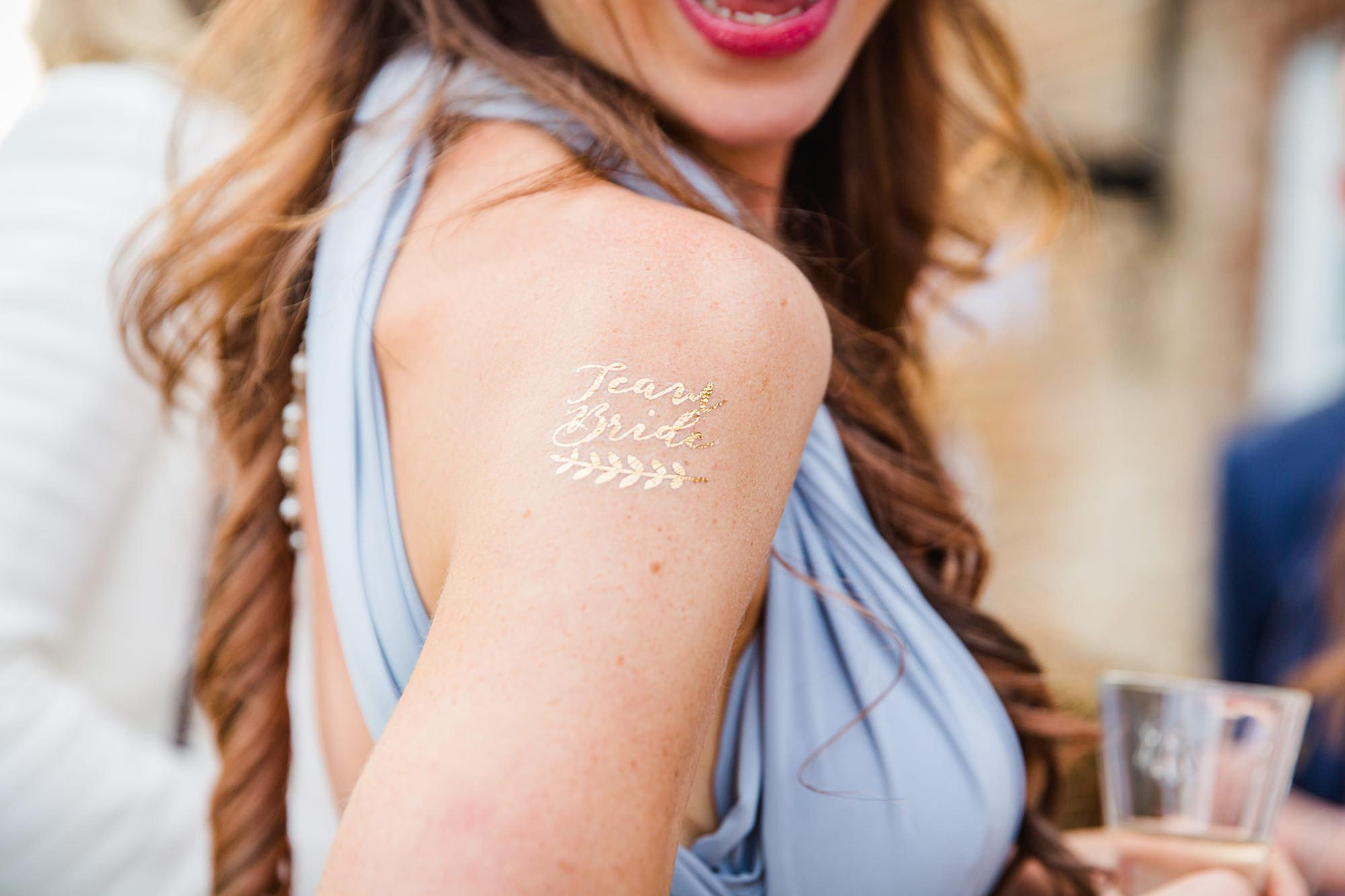 fun outdoor wedding close up detail of glitter tattoo