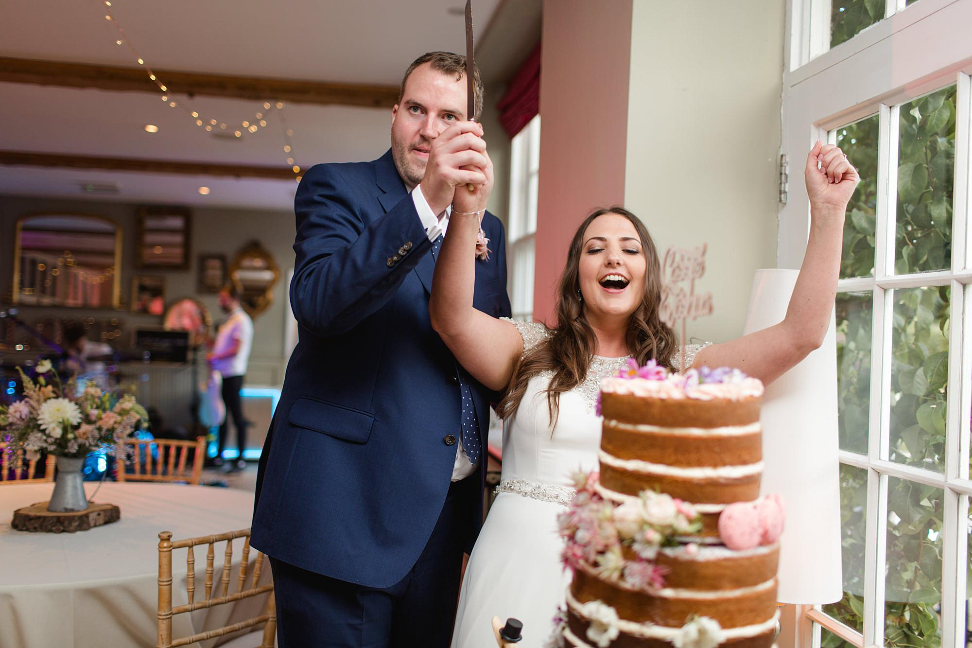 fun outdoor wedding fun portrait of bride and groom cutting cake
