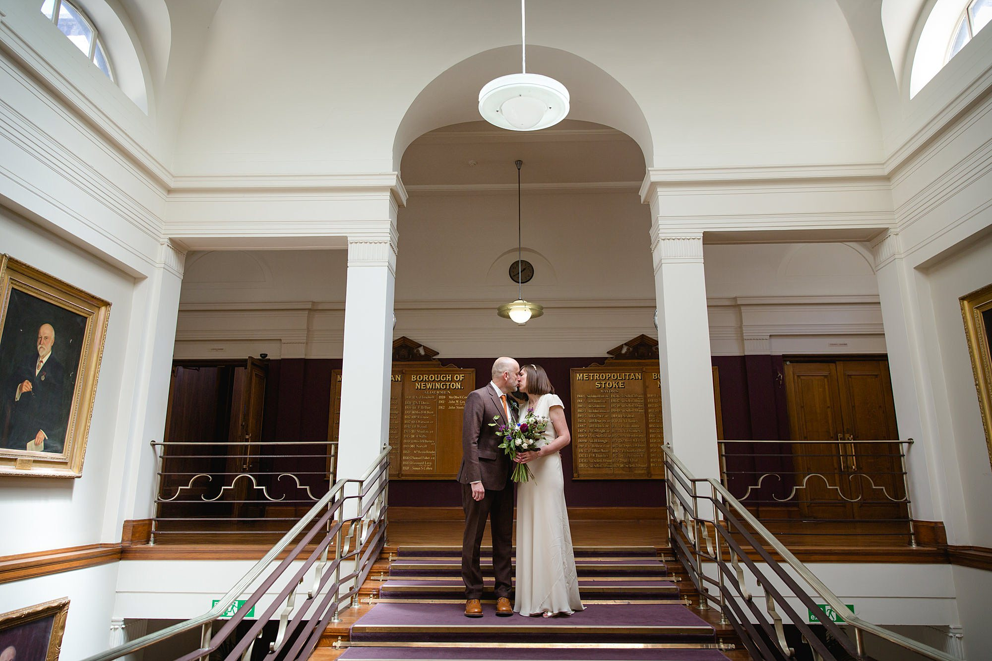 Clapton Country Club wedding photography bride and groom kiss on staircase