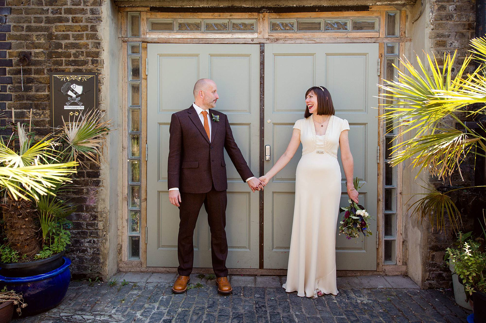 Clapton Country Club wedding photography groom and bride in front of doors