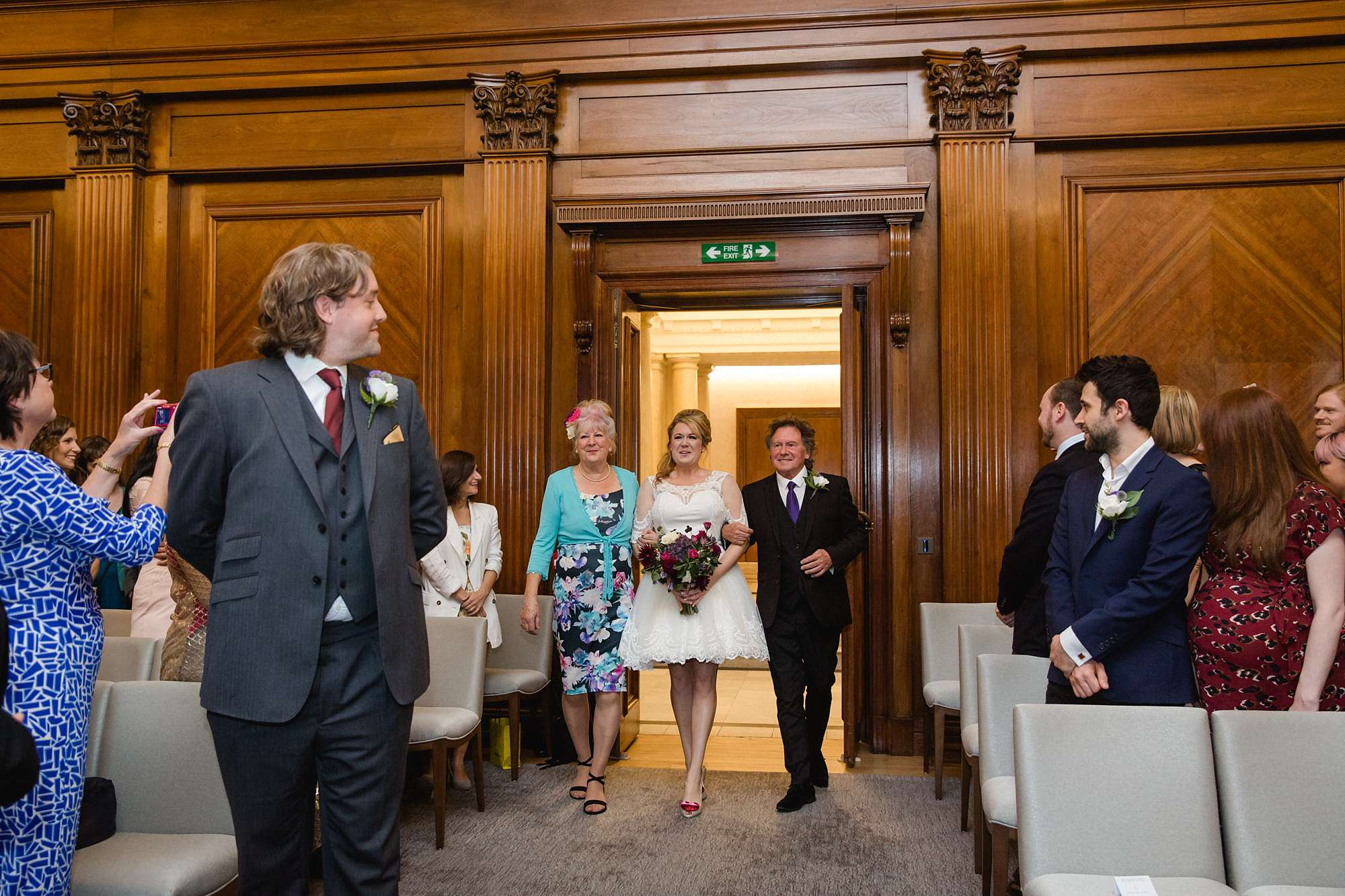 Old Marylebone Town Hall wedding photography bride and parents walk down aisle