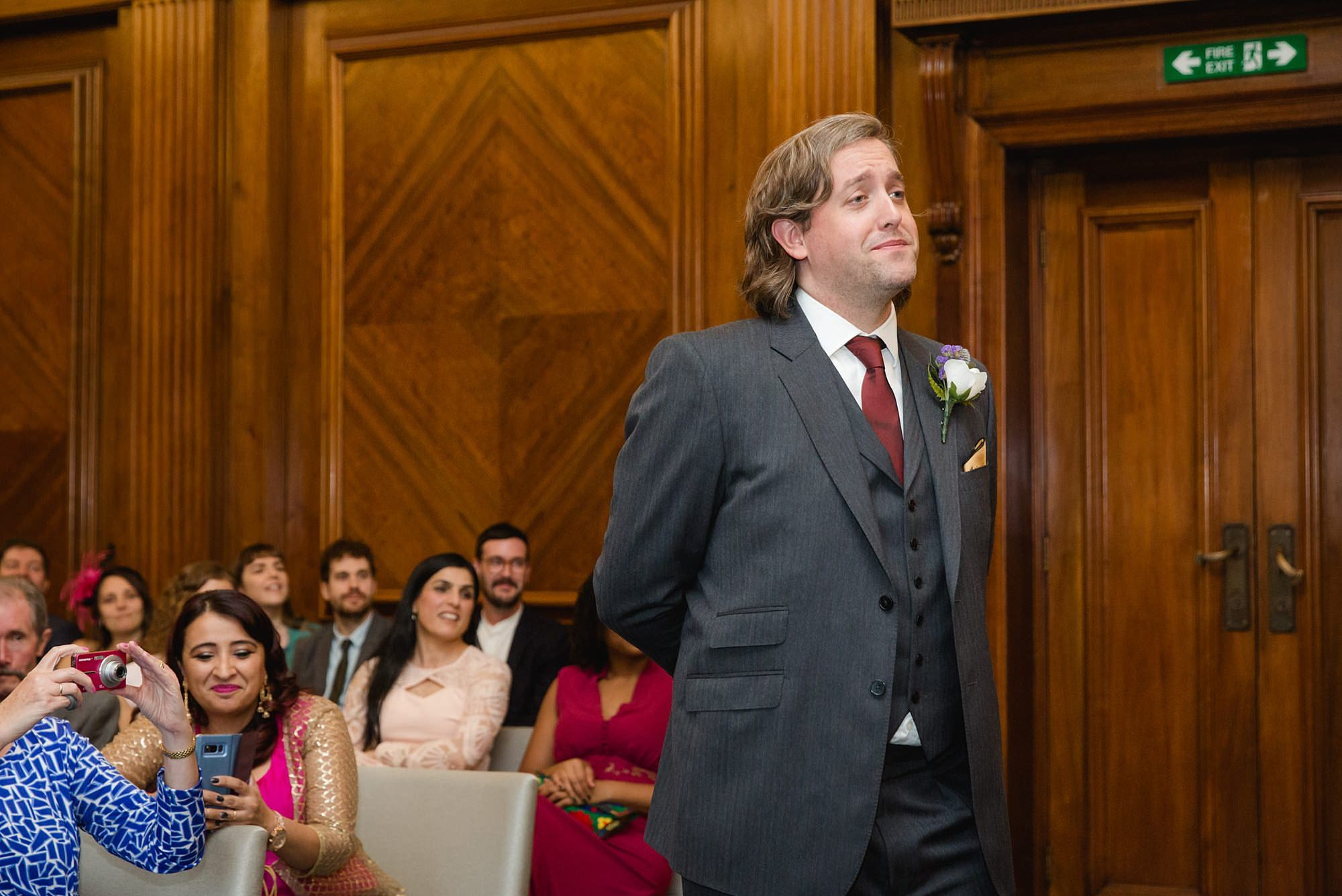 Old Marylebone Town Hall wedding photography groom watches choir sing