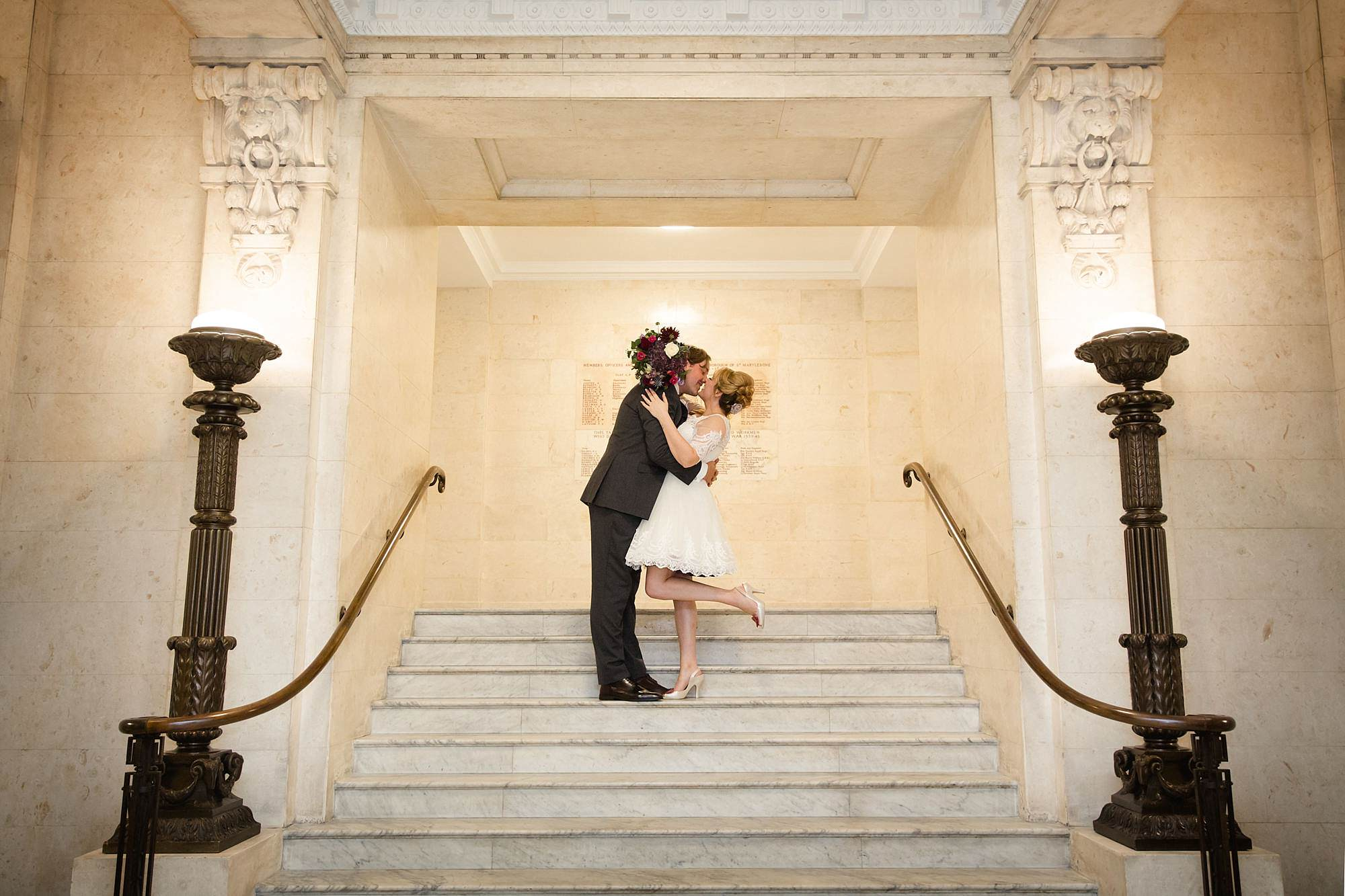 Old Marylebone Town Hall wedding photography couple kissing on stairs