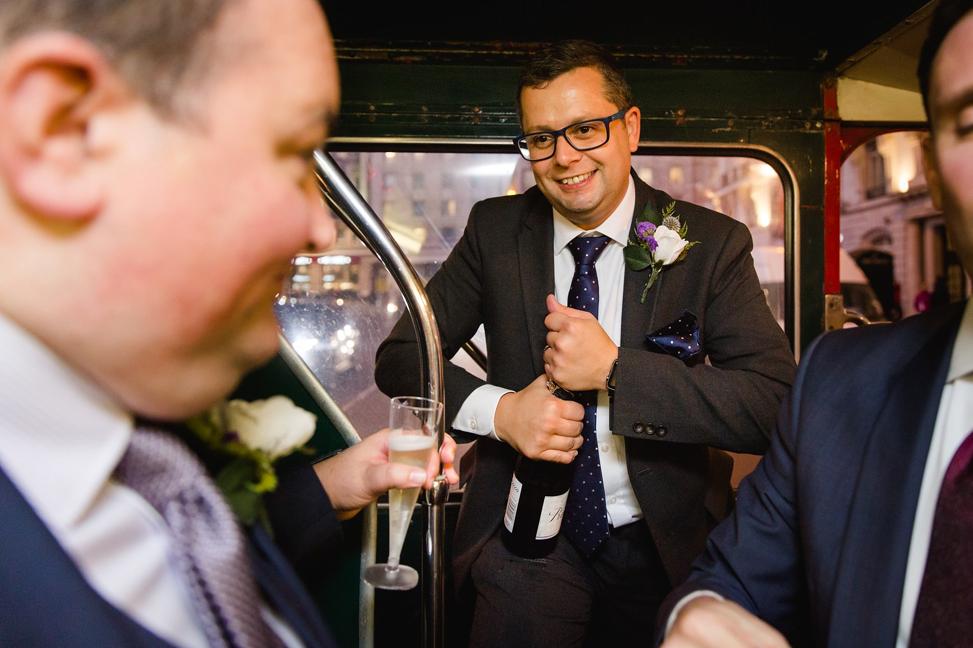 Old Marylebone Town Hall wedding photography groomsman opening champagne