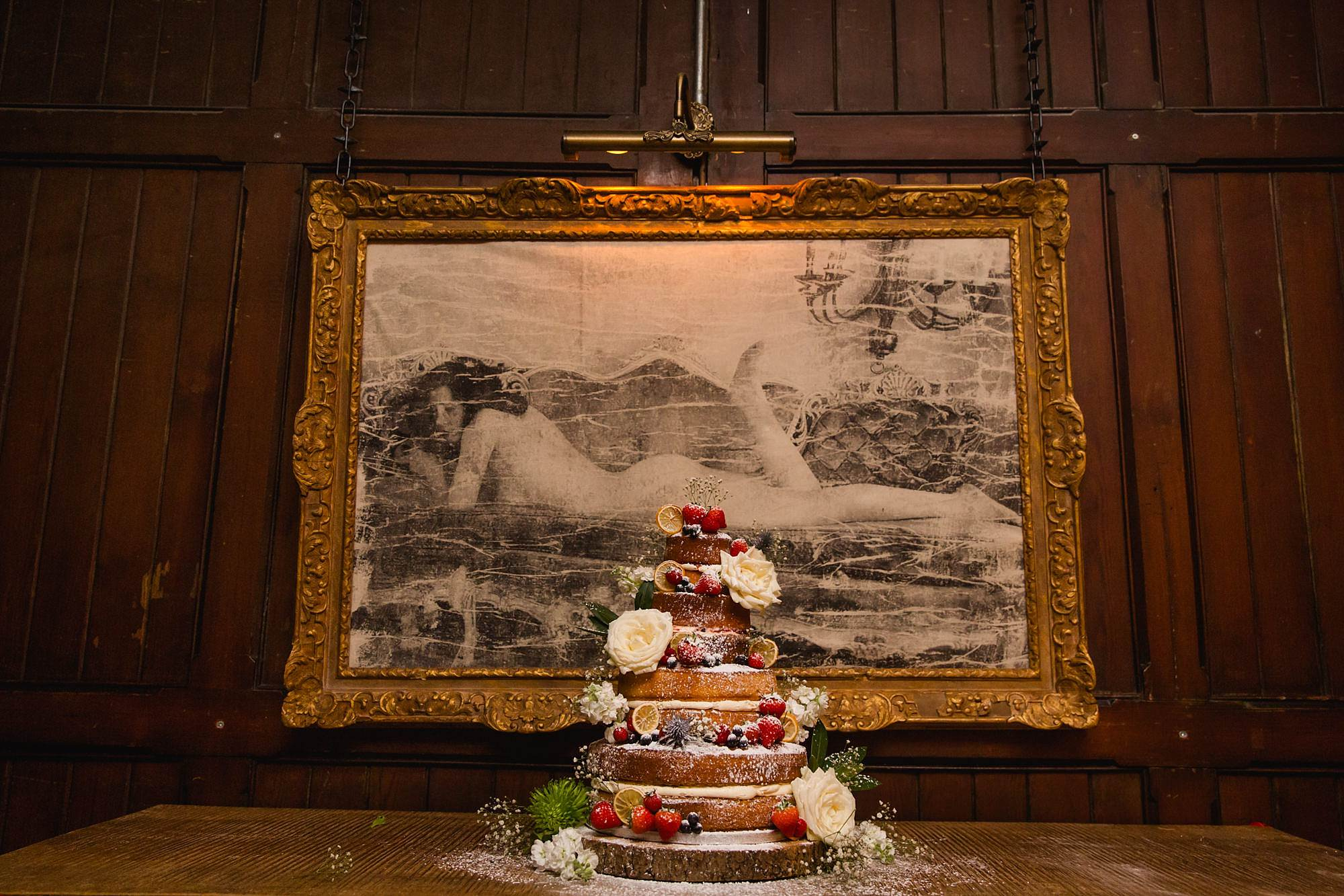 Old Marylebone Town Hall wedding photography wedding cake in front of painting