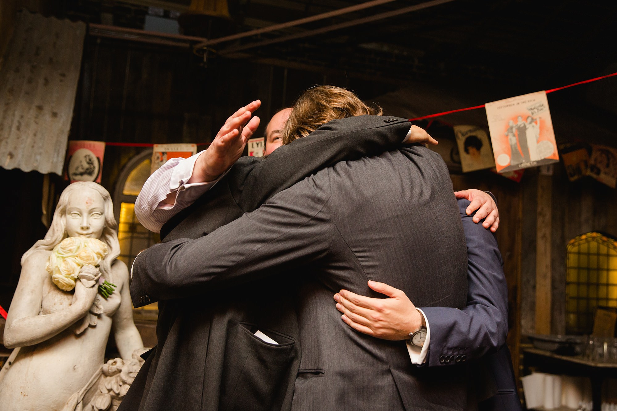 Old Marylebone Town Hall wedding photography groom and groomsmen hug