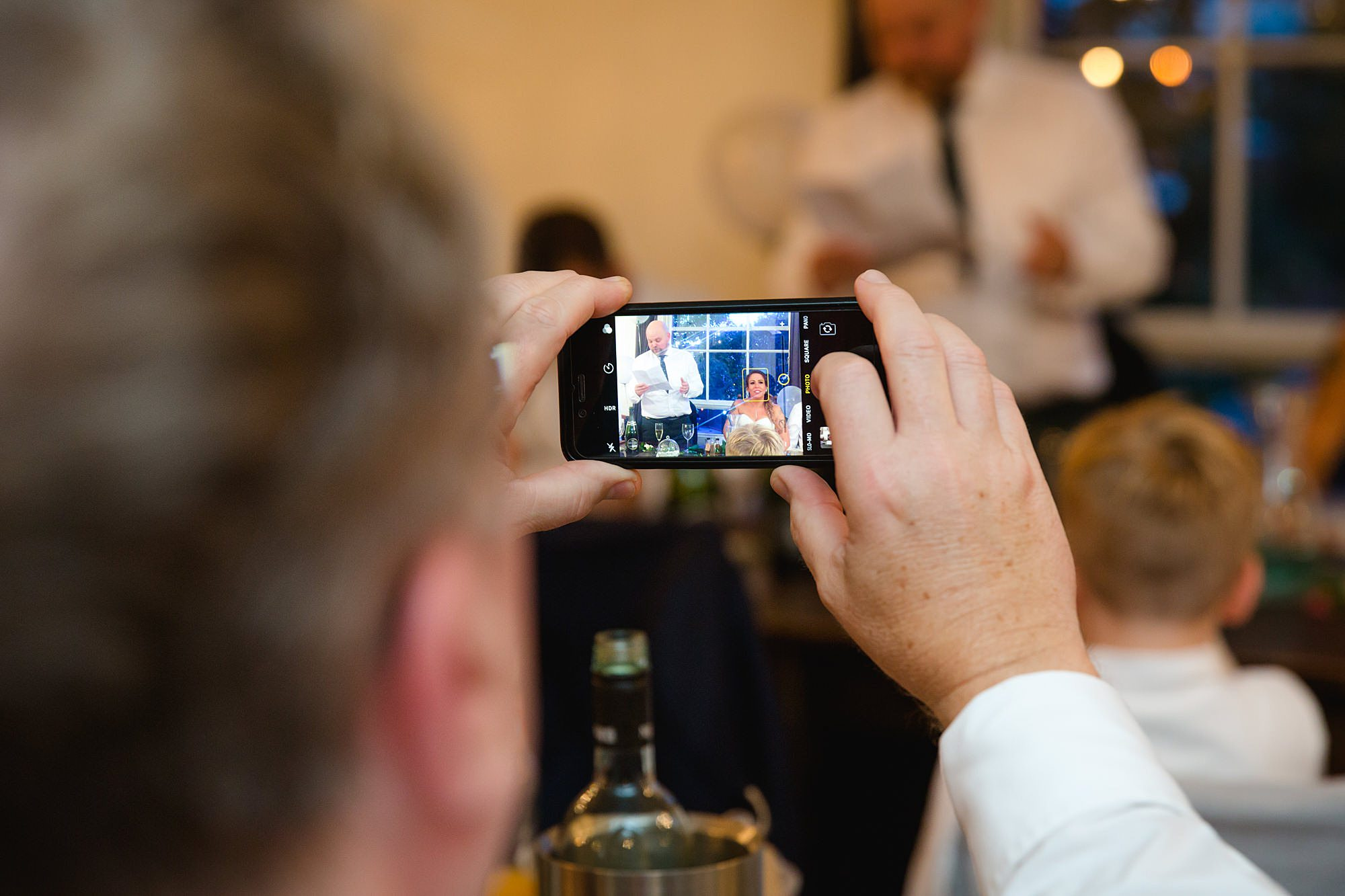 portraot of father of groom during speeches at prince albert pub guest takes a picture