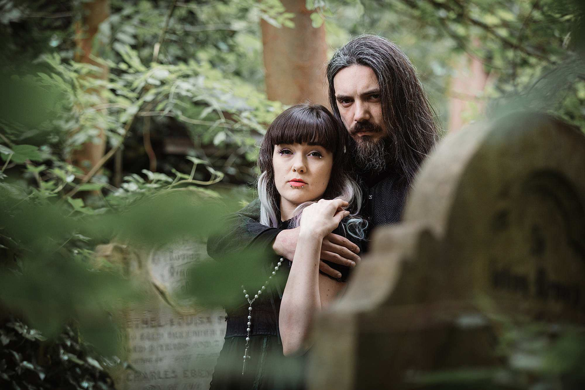 gothic engagement shoot couple cuddle together