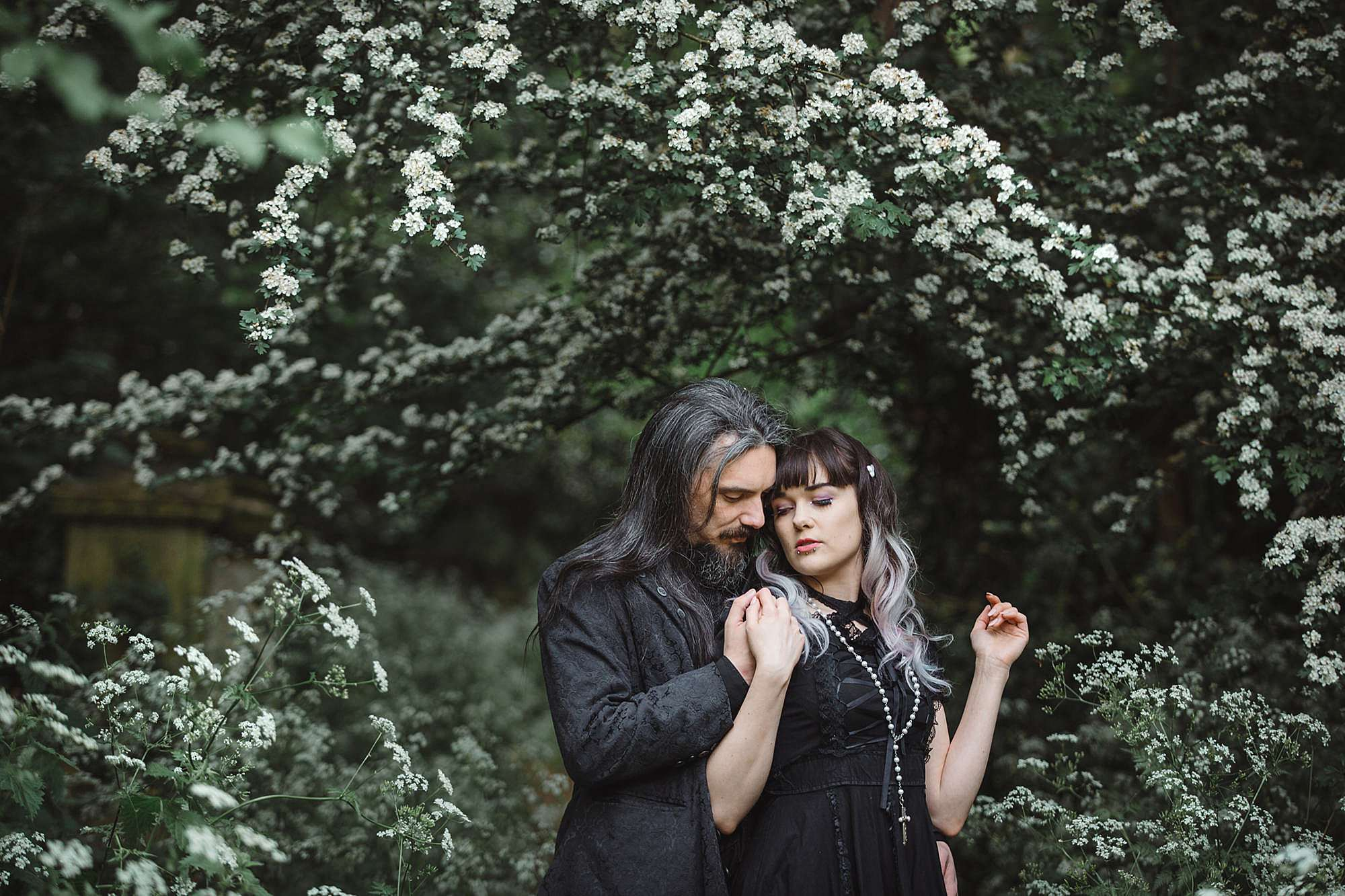 gothic engagement shoot by white flowers