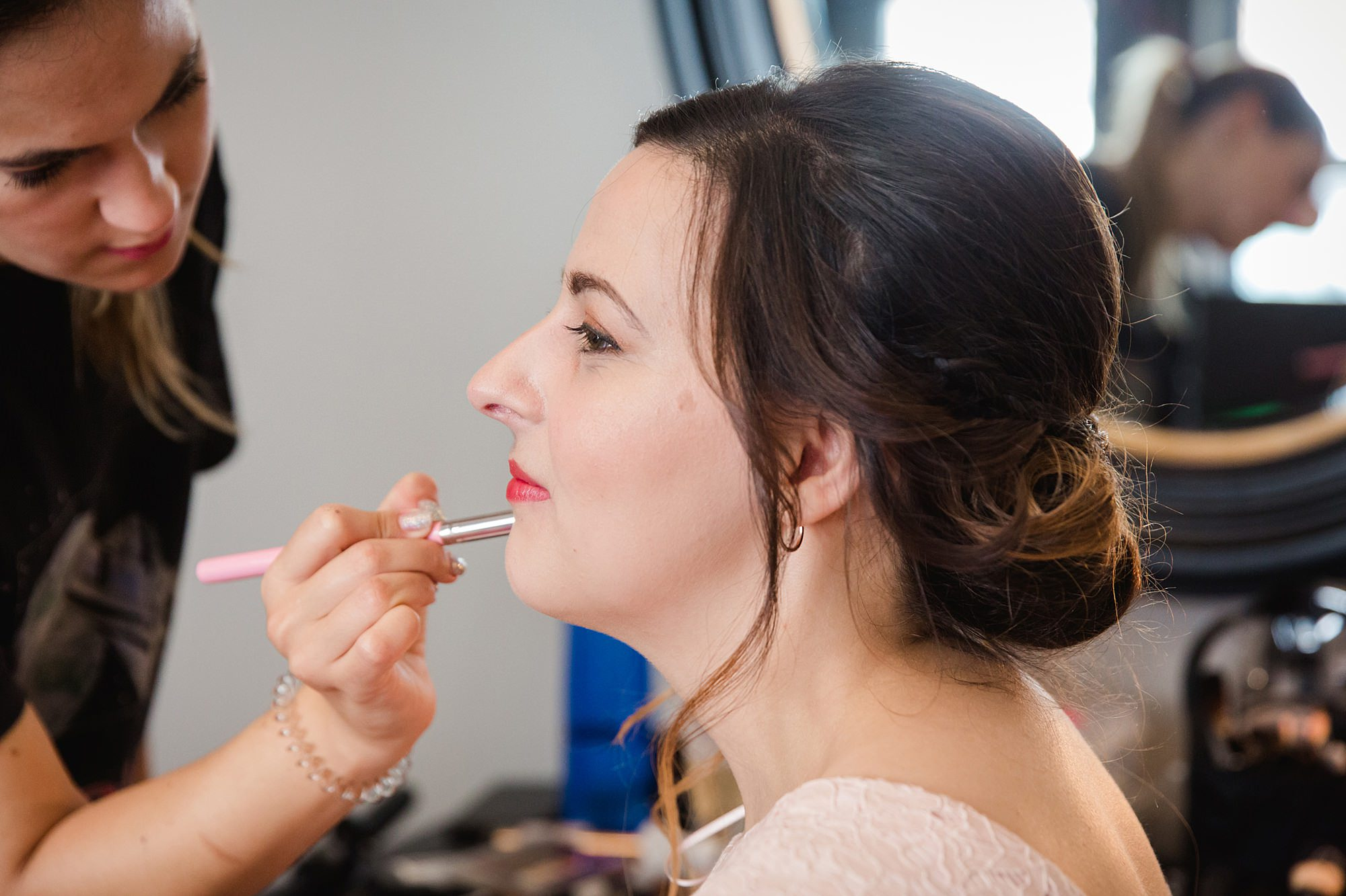 bridesmaid having lipstick applied ahead of Harrild and sons wedding