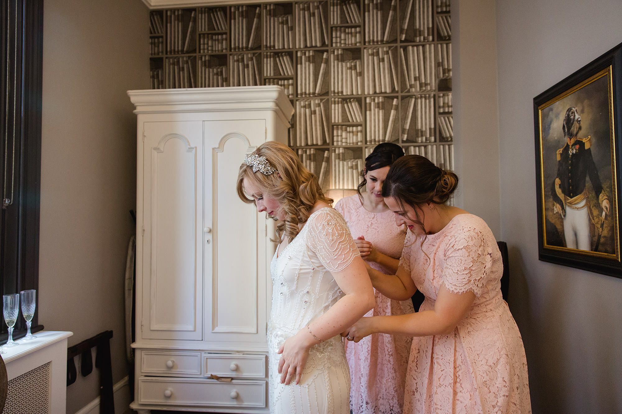 bridesmaids fasten bride into wedding dress